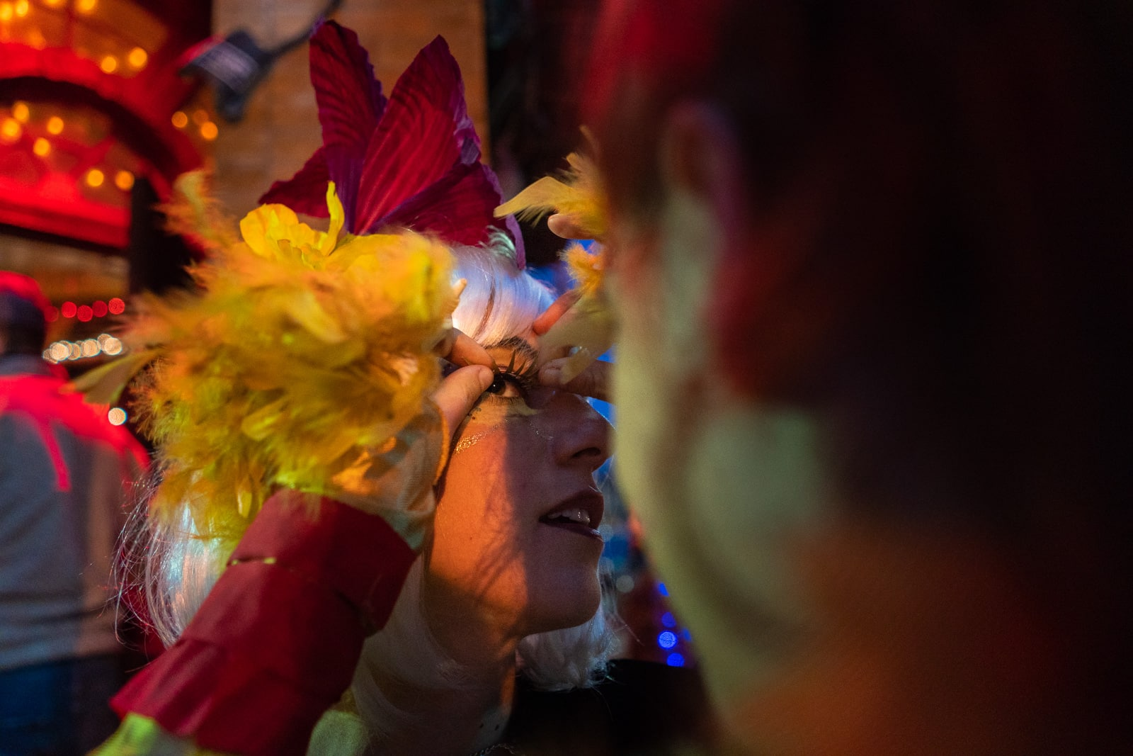 Gluing fake eyelashes onto a girl for a Mardi Gras parade in New Orleans
