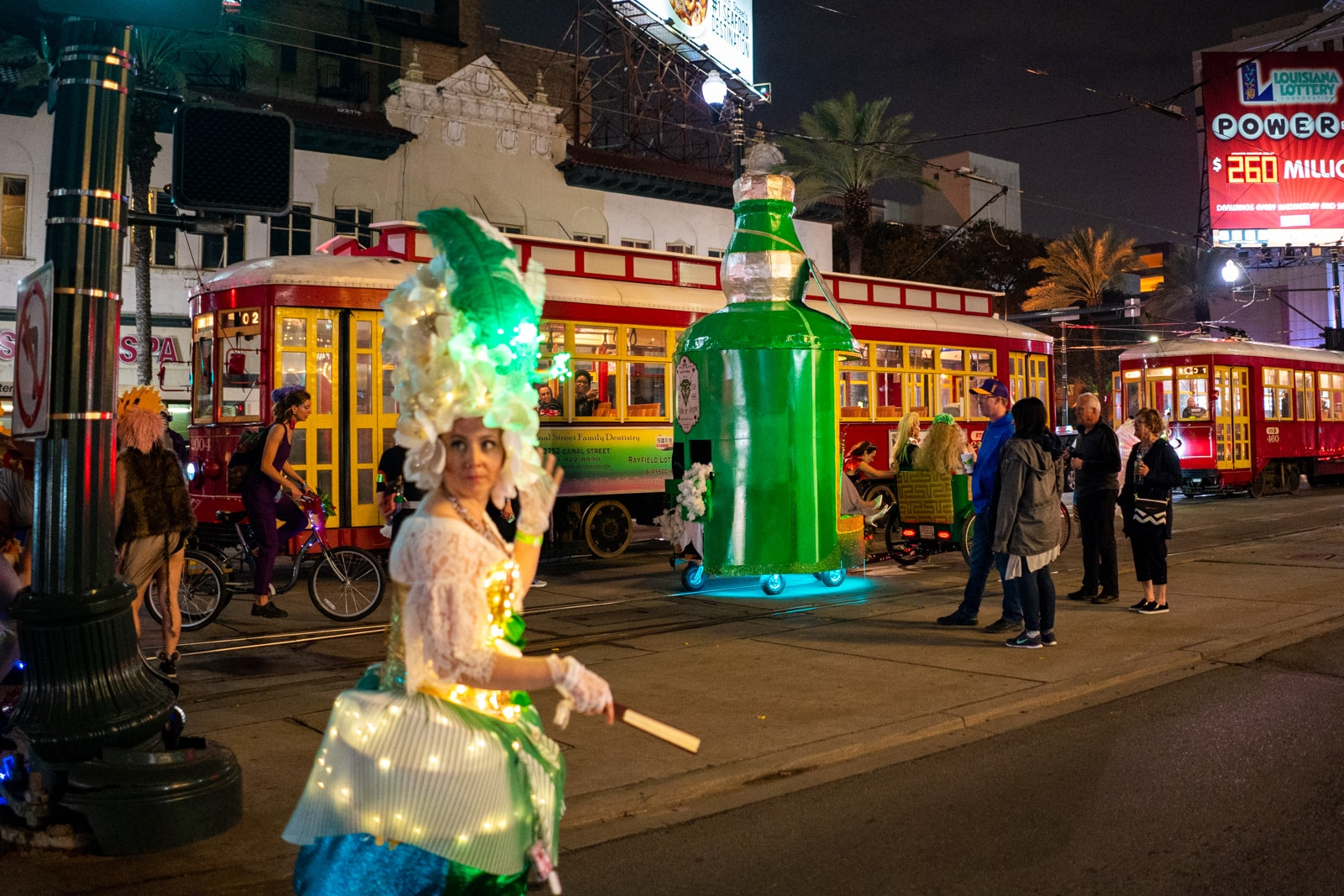 Paraders and floats exiting the parade next to a New Orleans street car