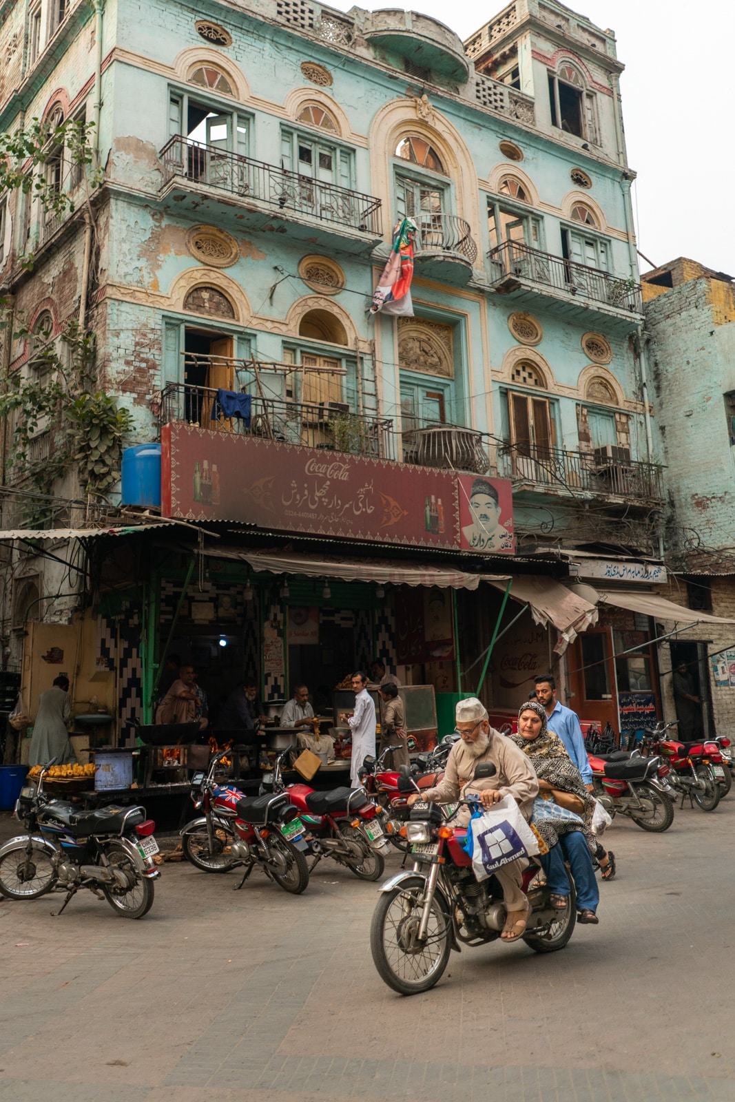 A couple driving a motorbike in front of a colorful building on Gawalmandi Food Street in Lahore, Pakistan