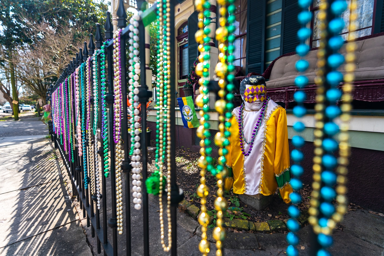 Mardi Gras beads on a fence with an Elvis statue in Algiers, near New Orleans