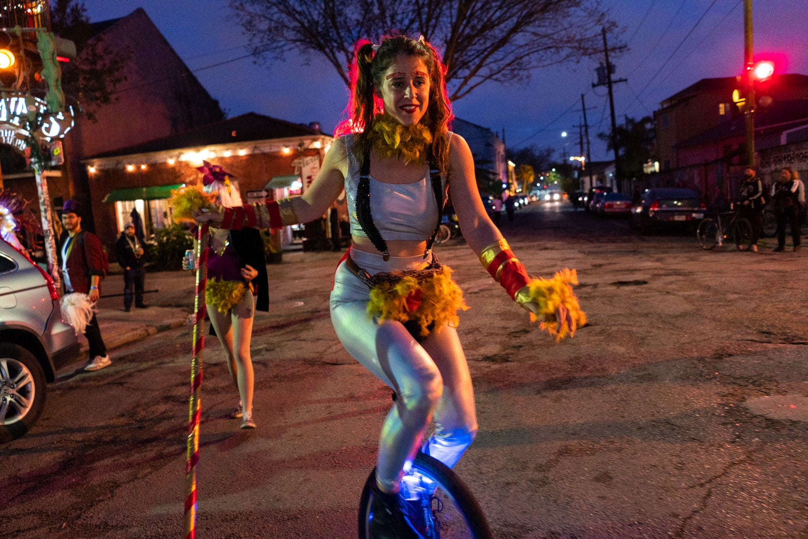 Girl riding a unicycle with a feathered fanny pack during Mardi Gras in New Orleans