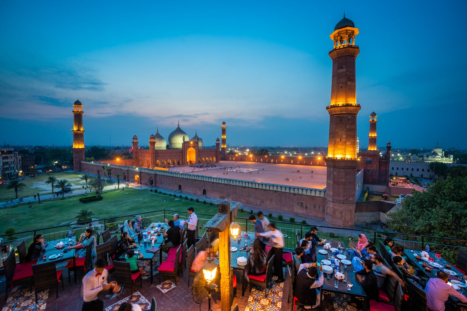 Badshahi Mosque in Lahore, Pakistan at sunset with people eating dinner a