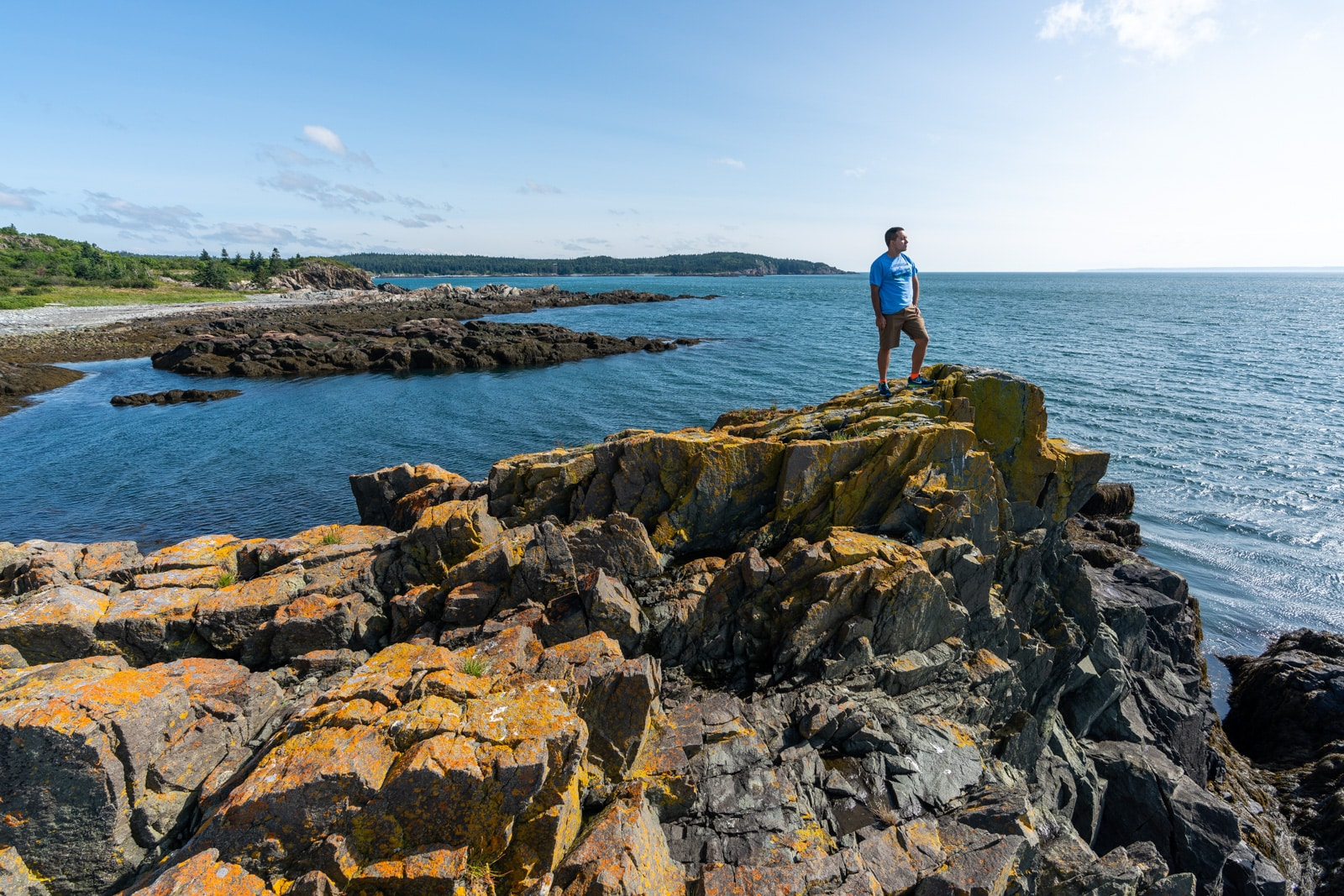 Brother standing on rocks on the Bold Coast near Lubec, Maine