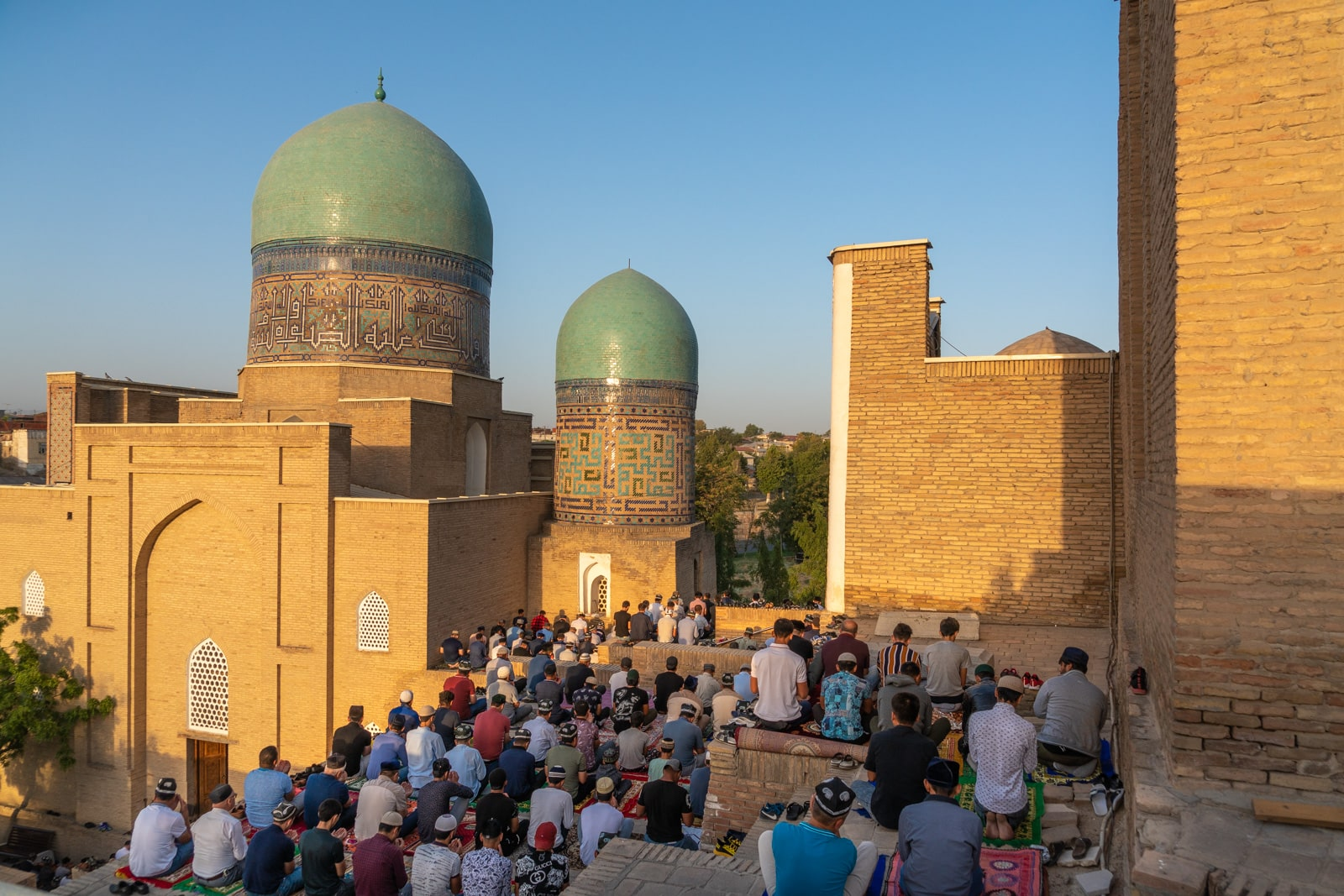Men praying for Eid outside the Shah-i-Zinda necropolis in Samarkand, Uzbekistan