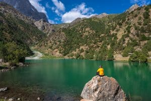 Sitting on rock during the Kulikalon Lake trek in Tajikistan's Fann Mountains