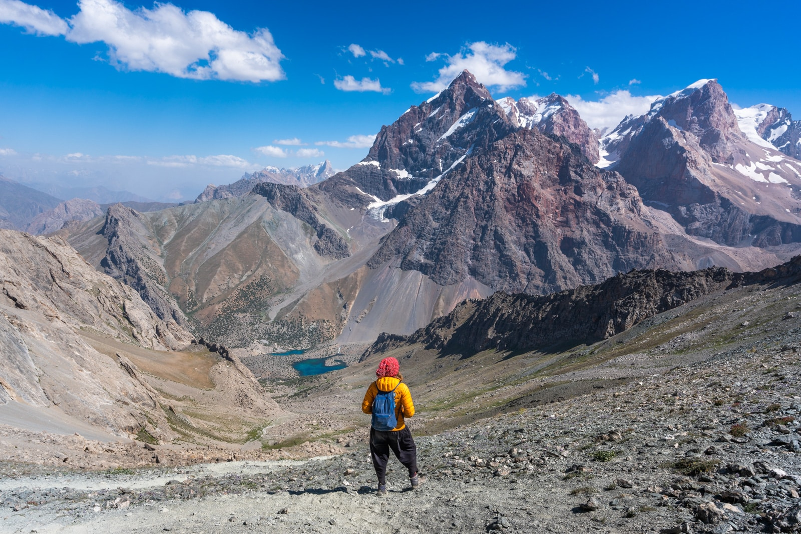 Trekker standing on Alauddin Pass overlooking Alauddin Lake in Tajikistan's Fann Mountains