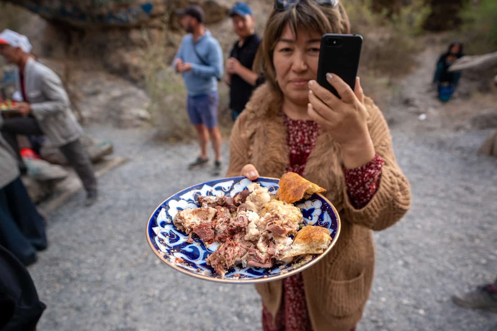 Woman offering a plate of mutton in Tajikistan