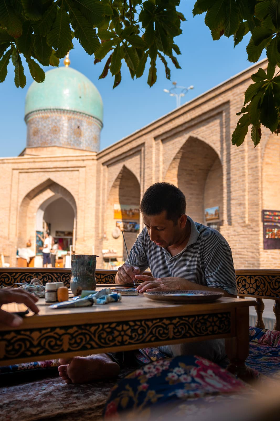 Artisan painting a plate in the Khast Imam complex