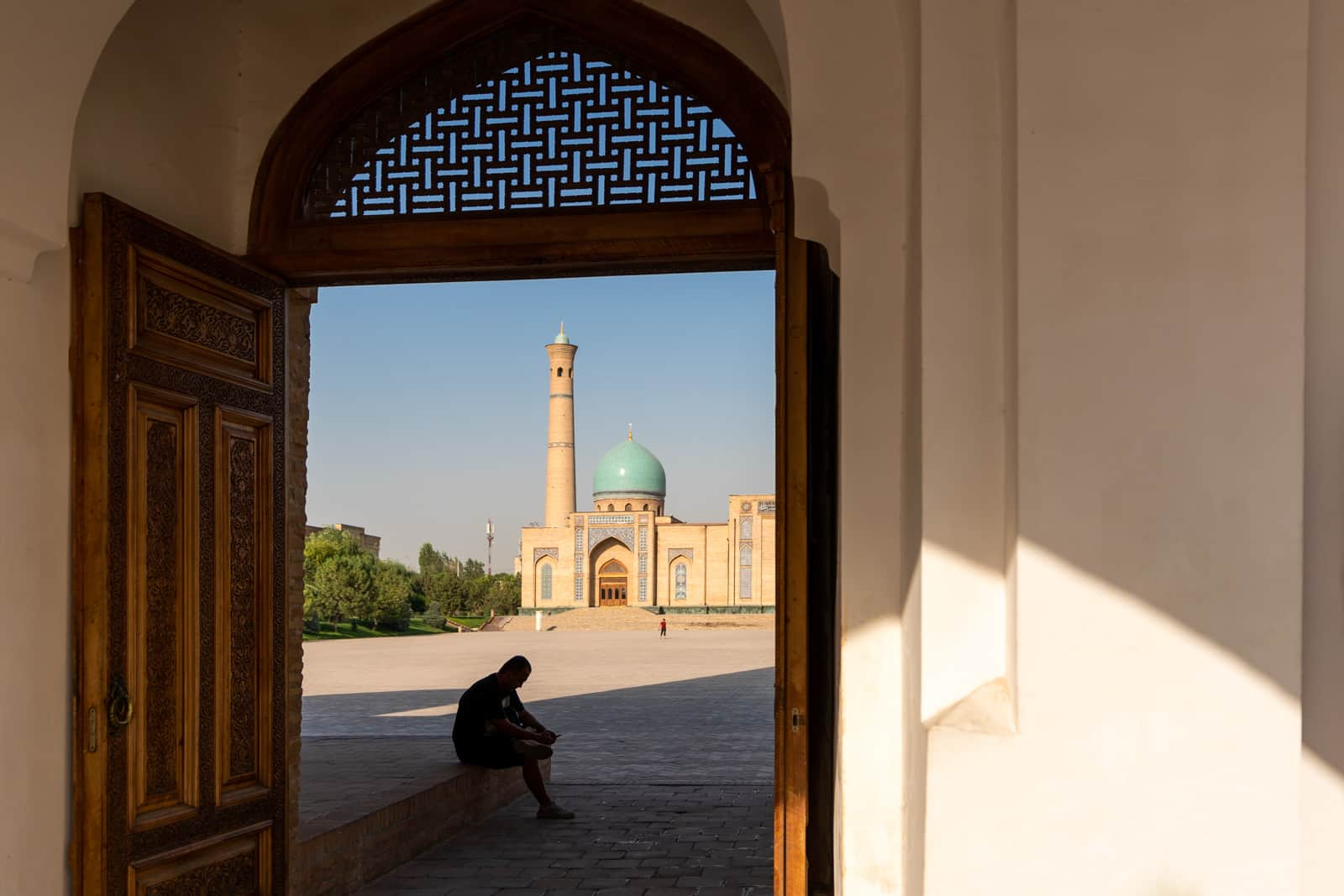 A man sitting in shadow in the Khast Imam complex in