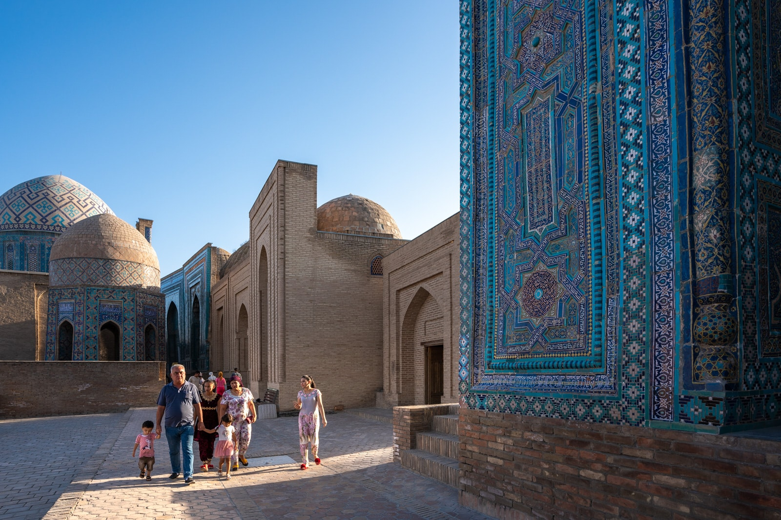 Family walking in evening at the Shah-i-Zinda necropolis in Samarkand, Uzbekistan