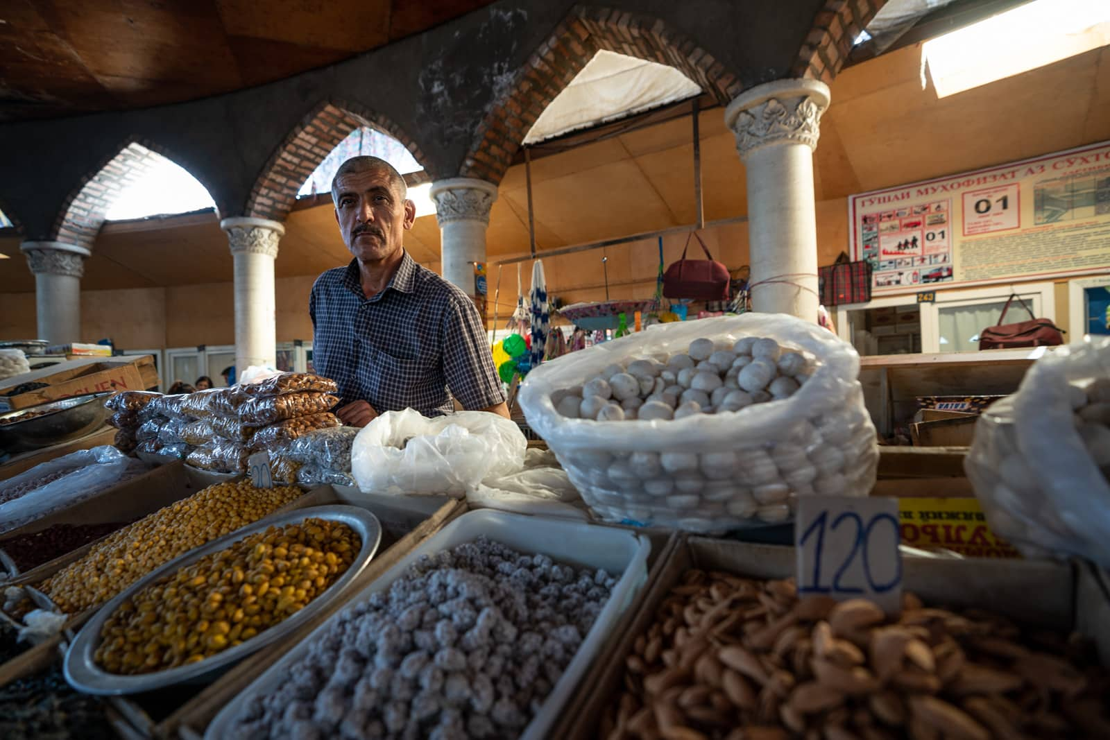 Man selling dried fruits and nuts in the Panjakent Bazaar in Tajikistan