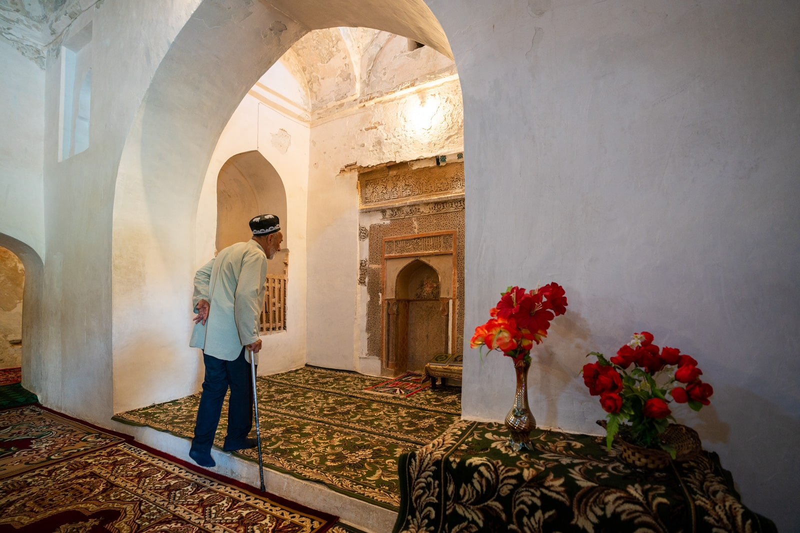 Caretaker walking in mausoleum of Muhammad Bashoro in Western Tajikistan
