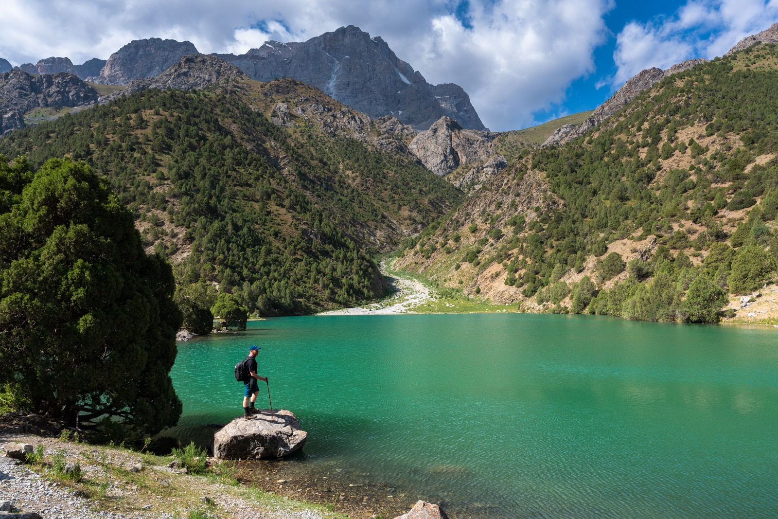 Trekker by a lake in Tajikistan's Fann Mountains