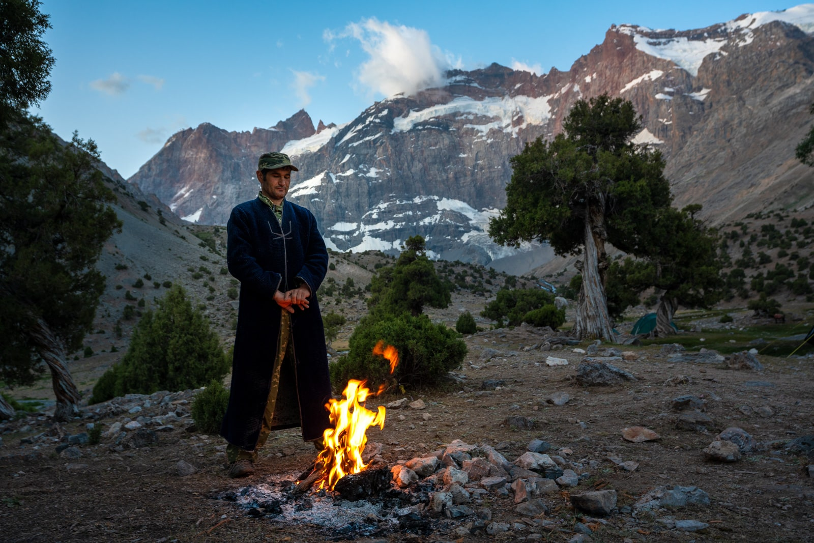 Porter warming himself by the fire in Tajikistan's Fann Mountains at sunrise