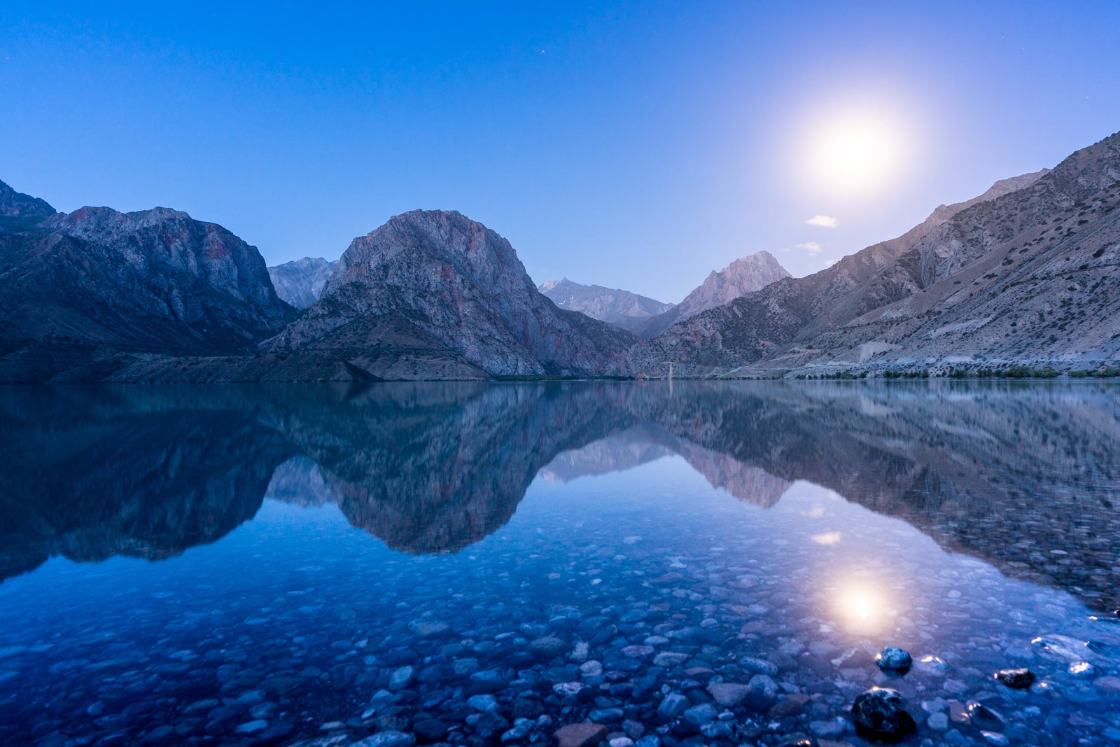 Blue hour and moon over Iskanderkul Lake in Tajikistan