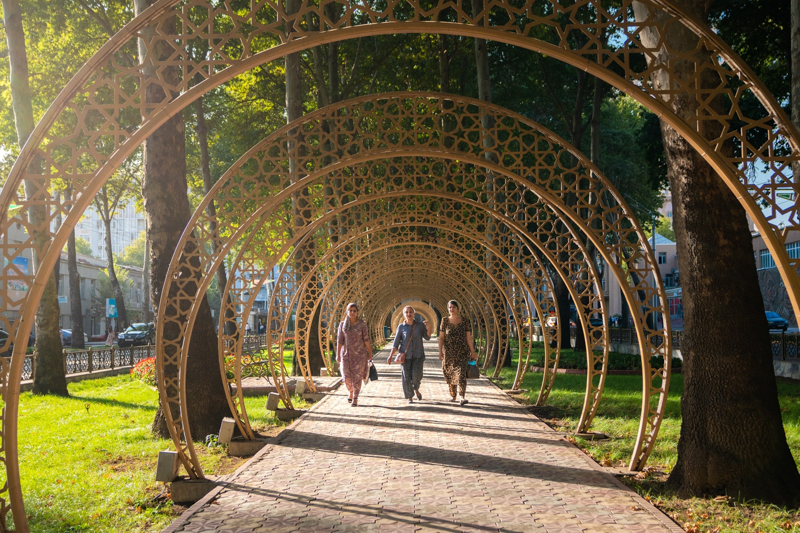 Women walking through a tunnel of arches in Dushanbe, Tajikistan