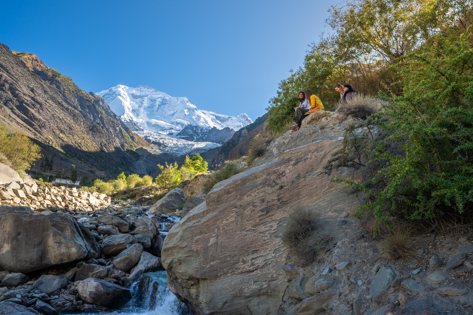 Girls sitting at a Rakaposhi viewpoint in Gilgit Baltistan, Pakistan