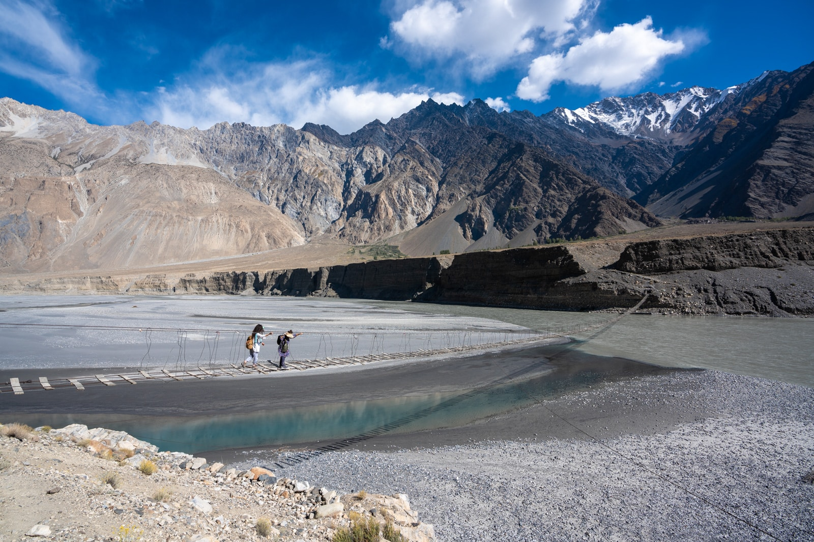 Women walking across the Passu Suspension bridge in Pakistan