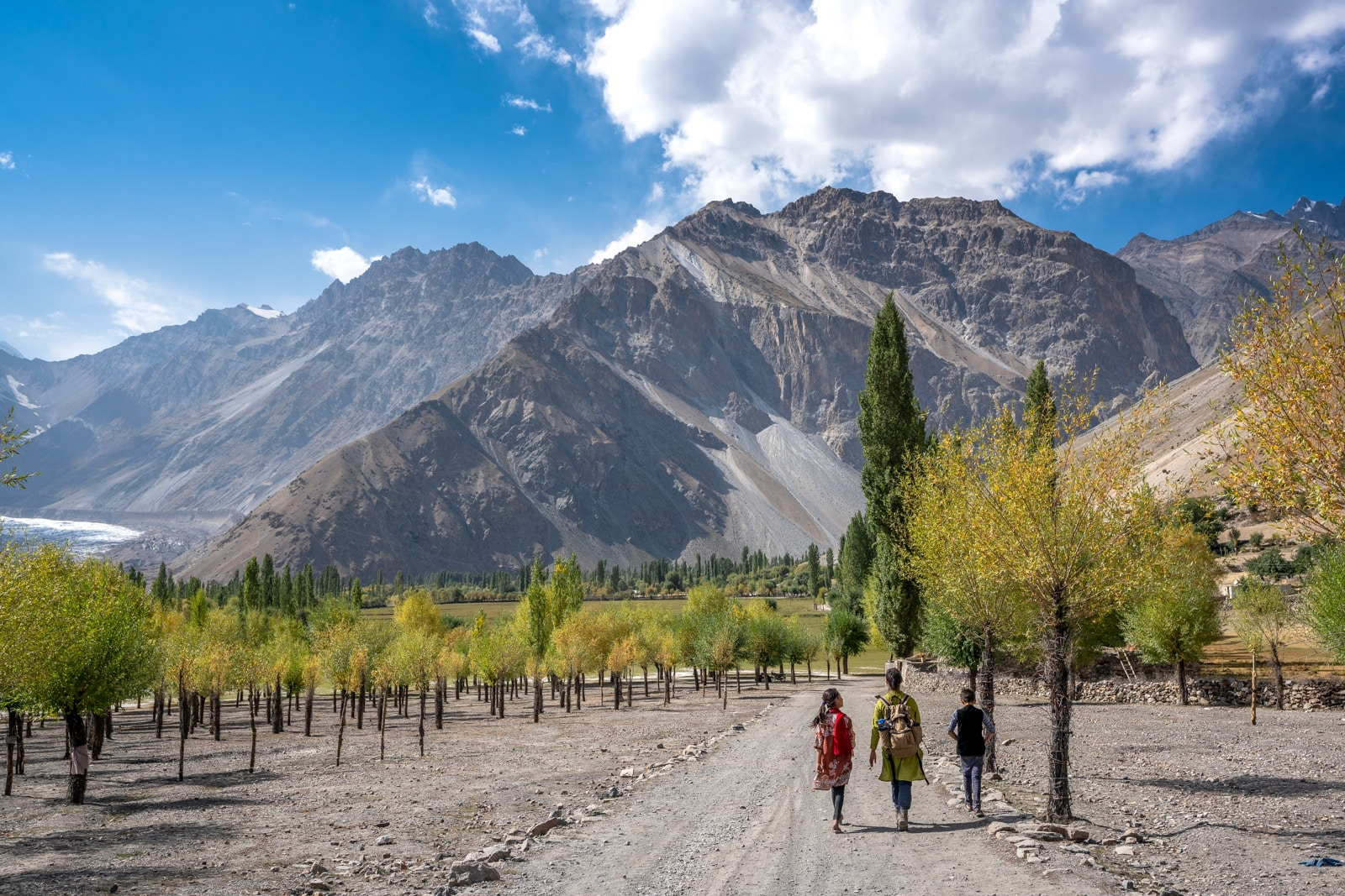Female traveler walking in Darkot, Pakistan with local family