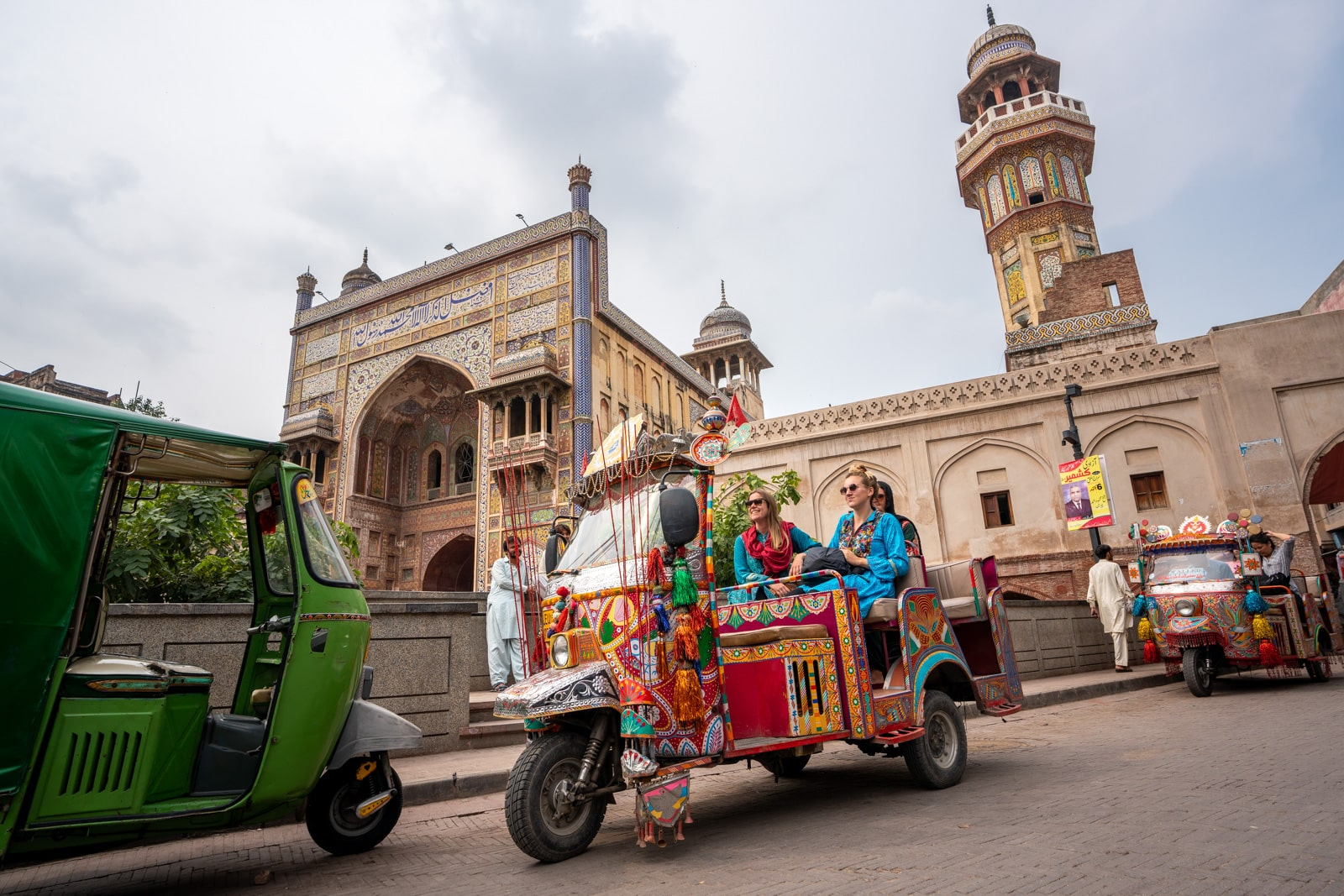 Girls sitting in a rangeela rickshaw outside of Wazir Khan Mosque in Lahore, Pakistan