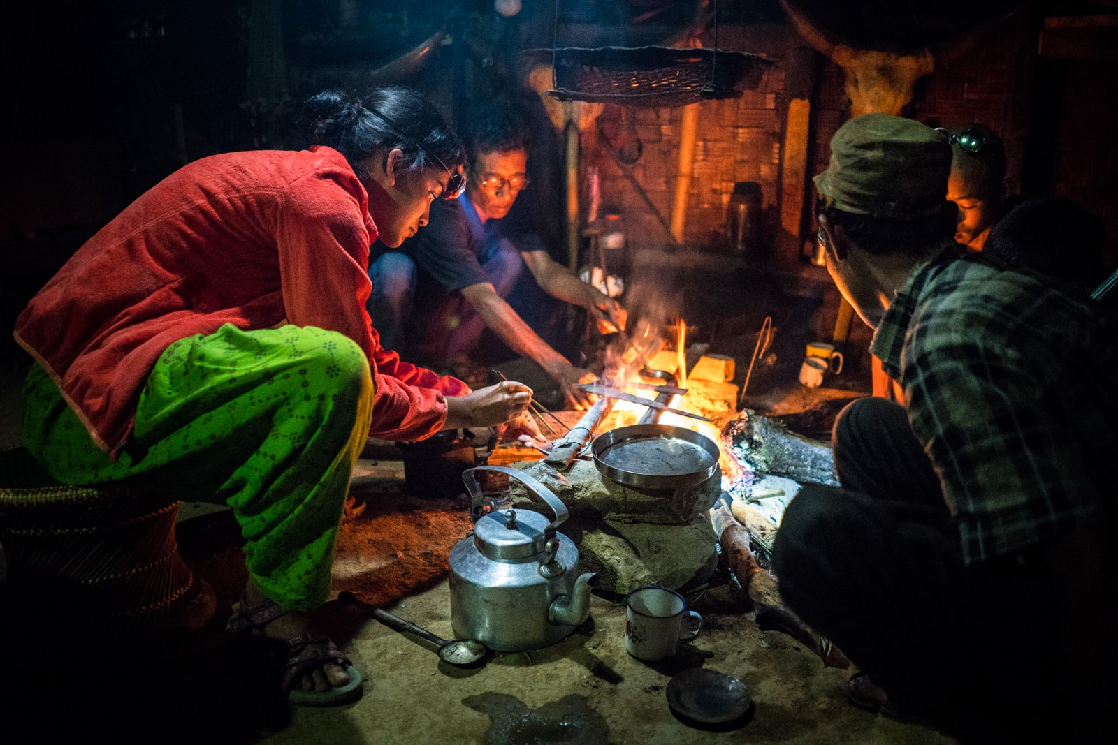Backpacker cooking opium in Longwa, Nagaland, India with a headlamp