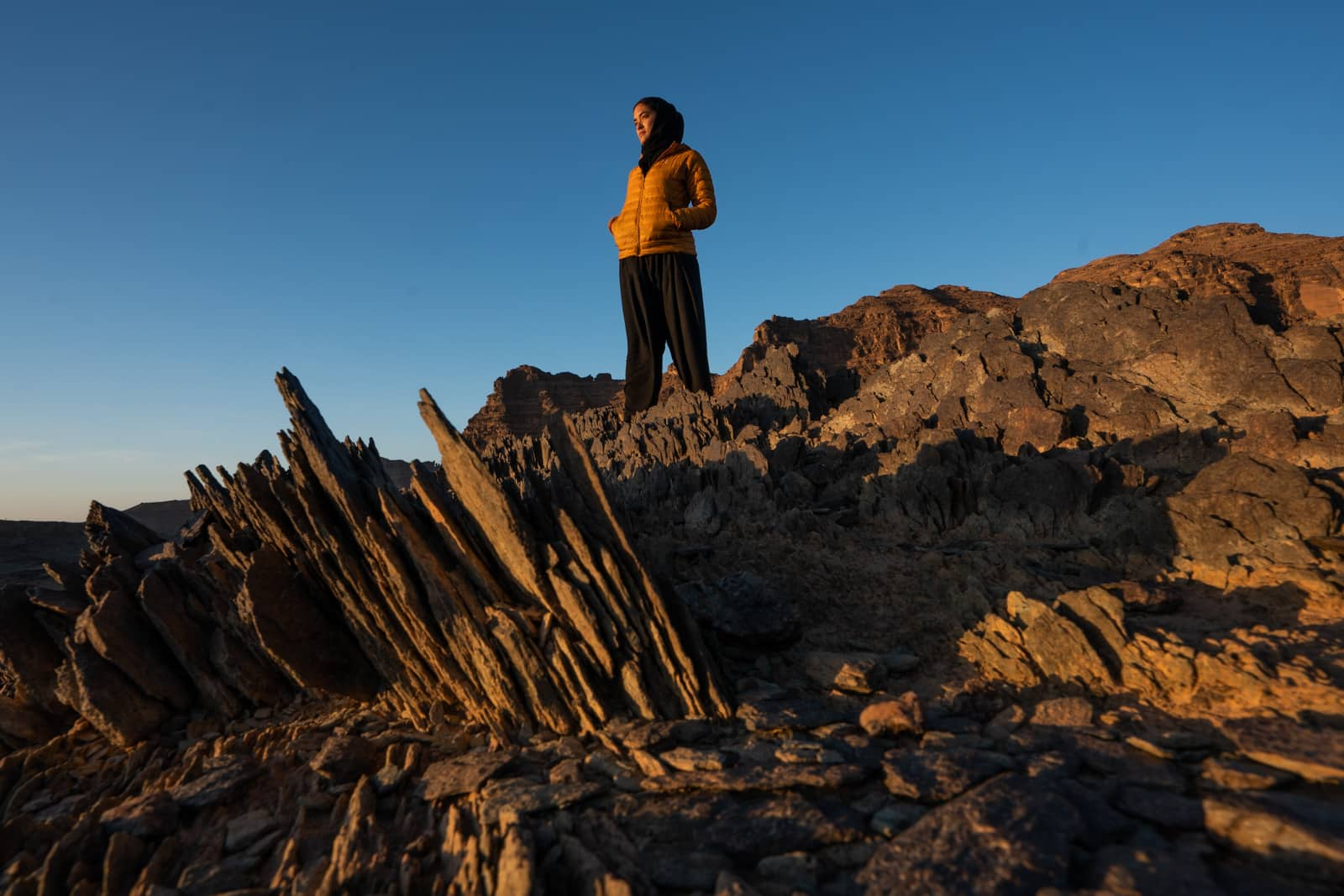 Female traveler in Saudi Arabia watching a sunrise over mountains in Najran