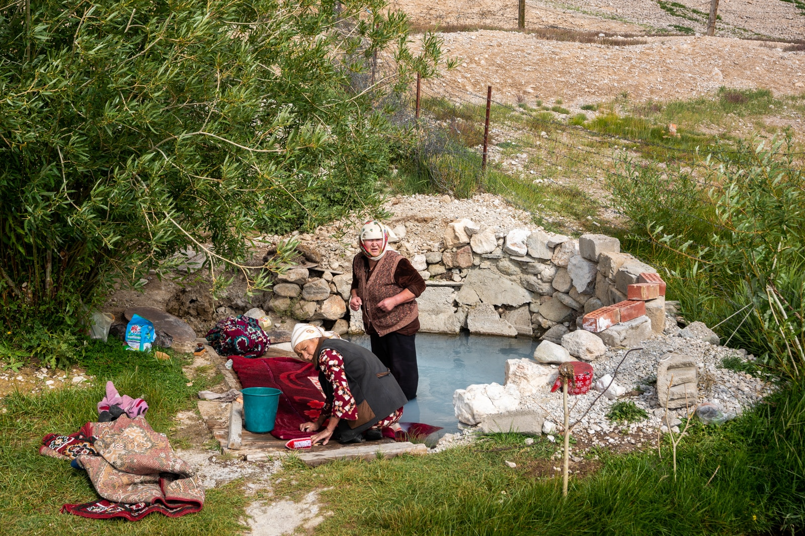 Women washing clothes in a fish pond in Shaimak Village, Pamir Mountains, Tajikistan