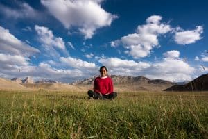 Female traveler sitting in the grass in Tajikistan's Pamir mountains near Shaimak Village