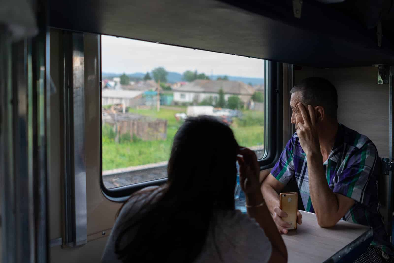 Man looking out window on train to Severobaikalsk, Siberia, Russia