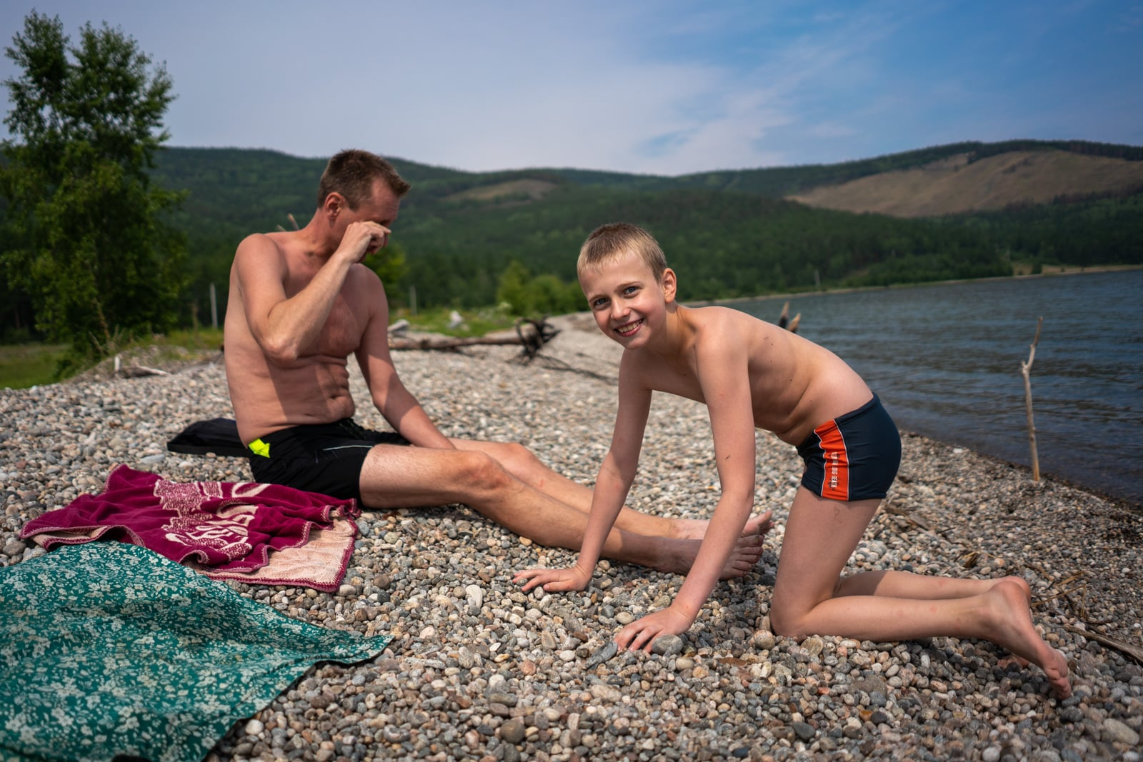 Father and son playing on a pebble beach in north Lake Baikal, Siberia, Russia