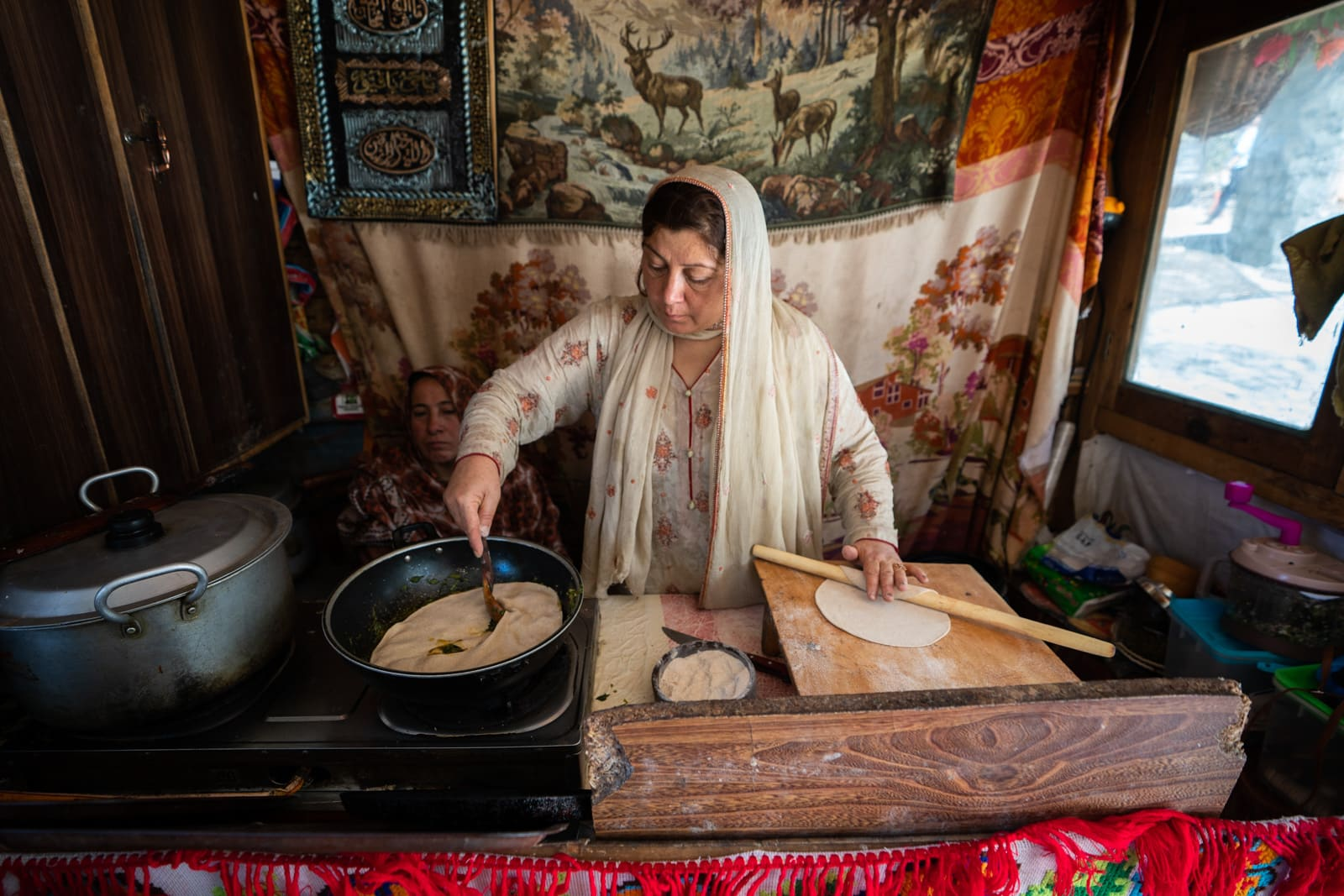 Female entrepreneur and business owner cooking at her cafe in Karimabad, Hunza, Pakistan