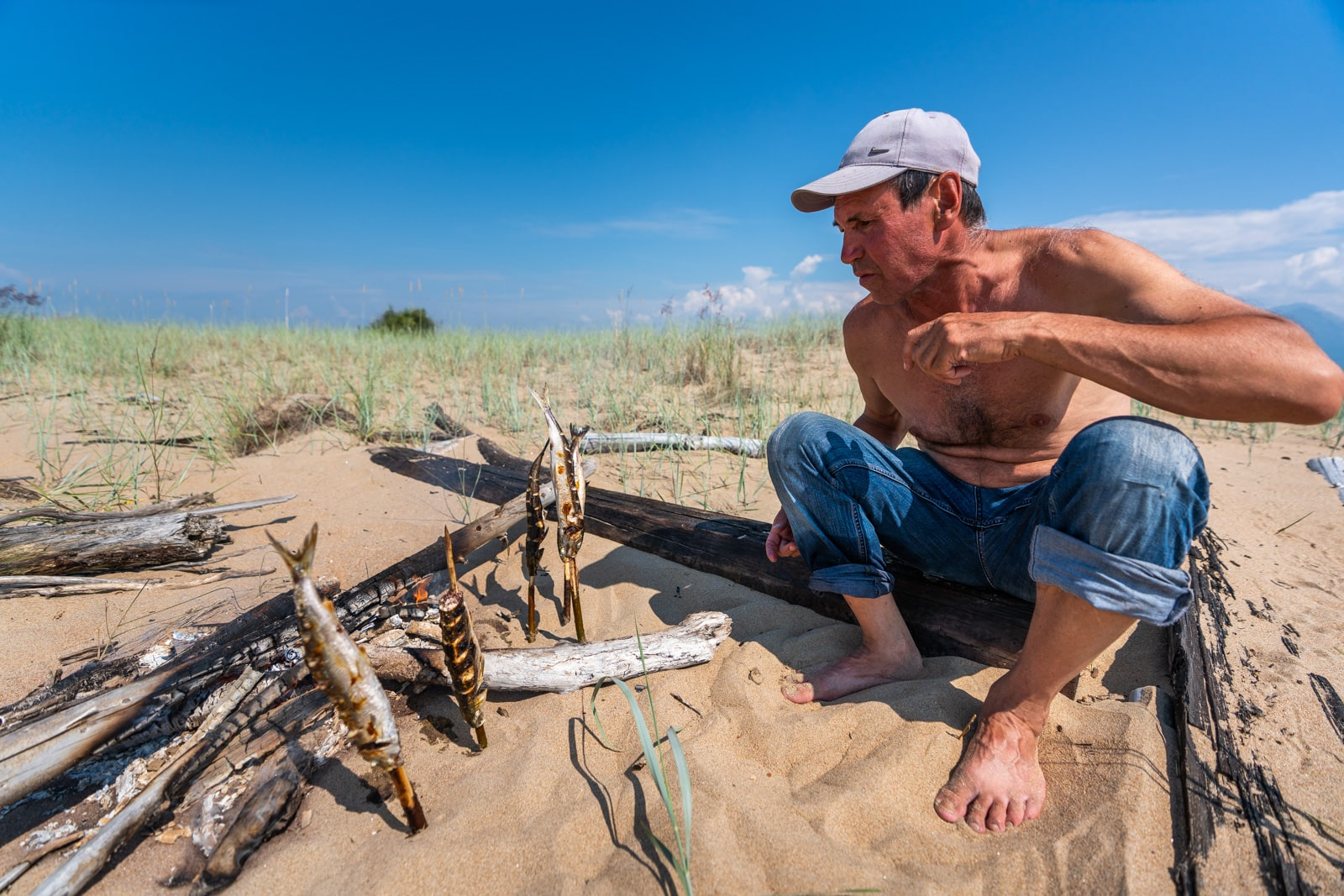Man barbecuing omul fish on the beach of northern Lake Baikal, Siberia, Russia