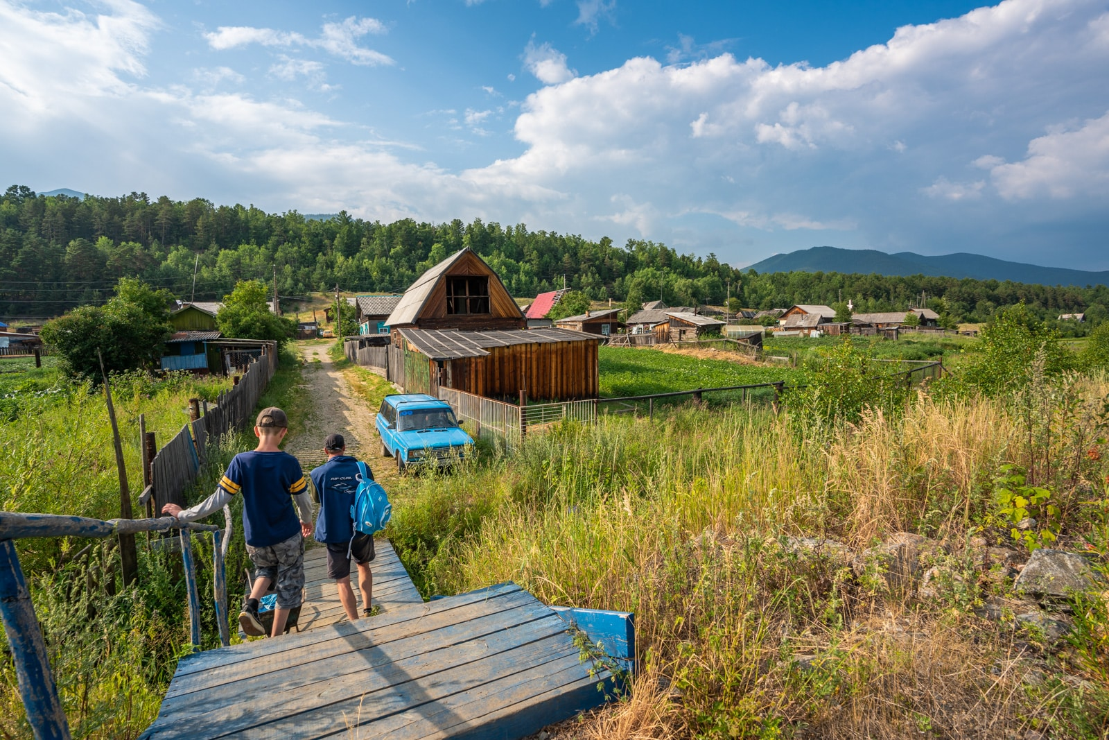 Father and son walking in Dushkachan village near Severobaikalsk, Siberia, Russia