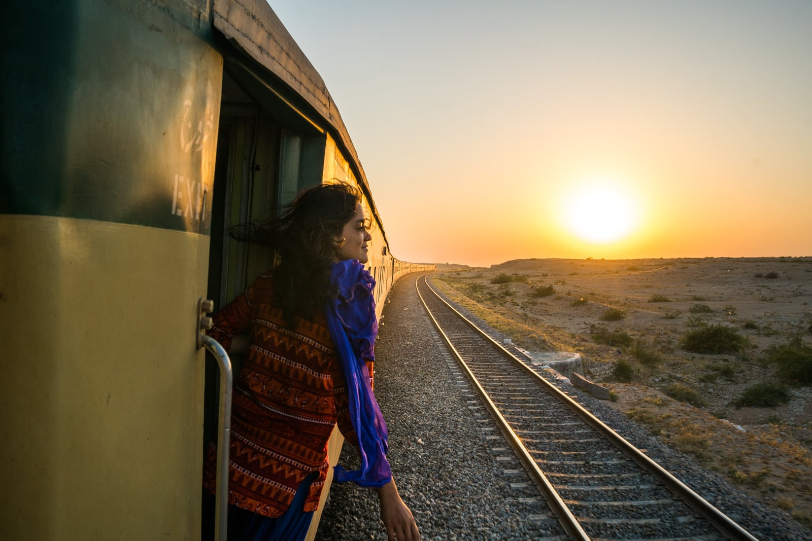 Female traveler riding a train from Lahore to Karachi, Sindh, Pakistan, at sunset