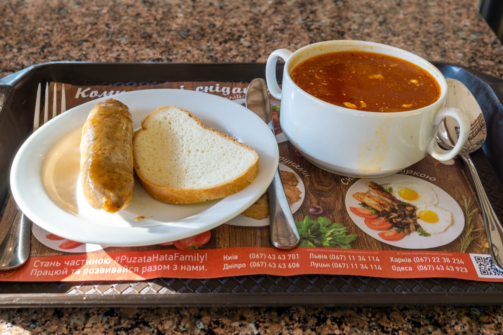 A typical cafeteria meal in Ukraine with sausage and borsch and bread
