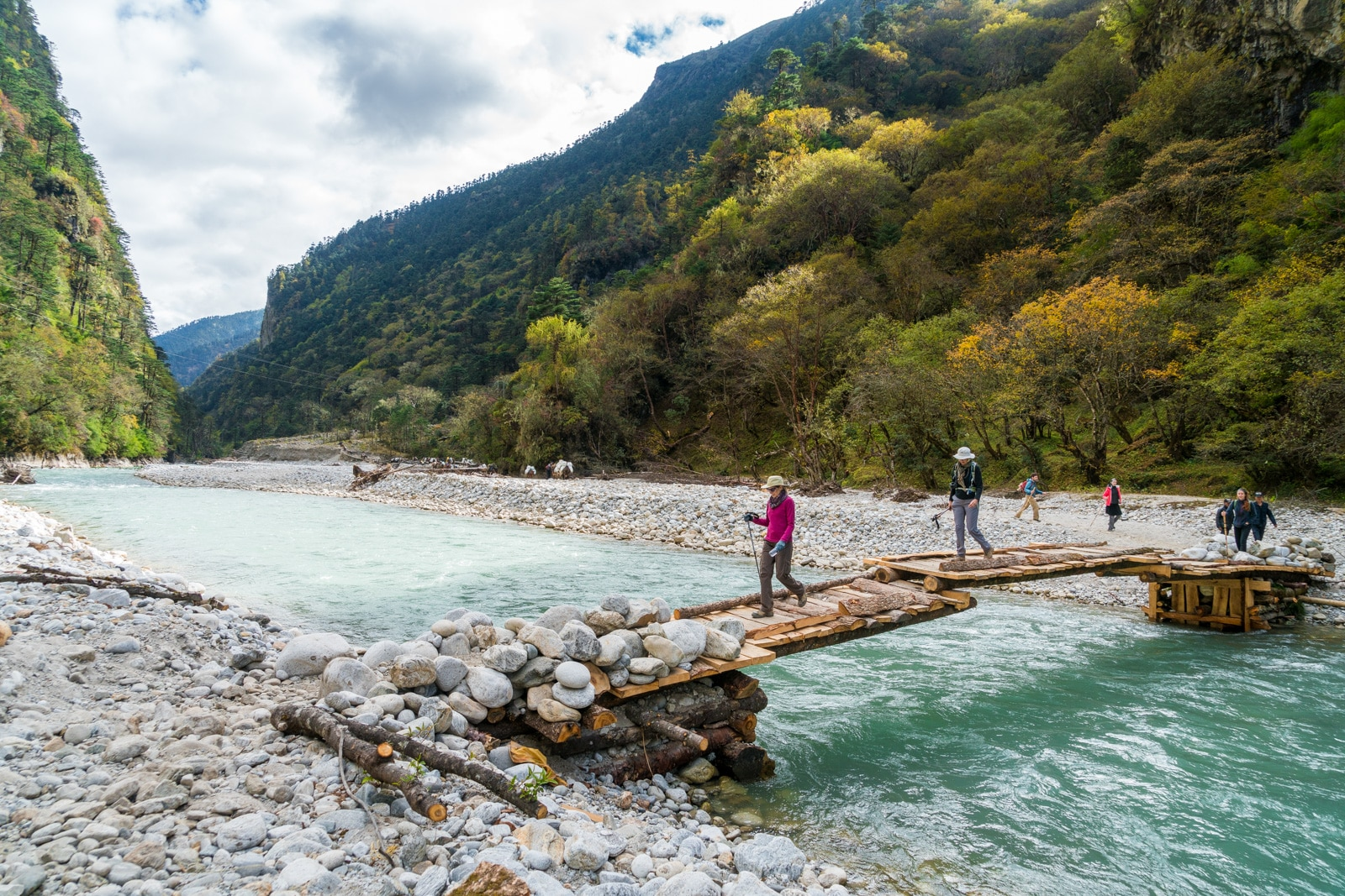 Tourists walking across a bridge over a small river