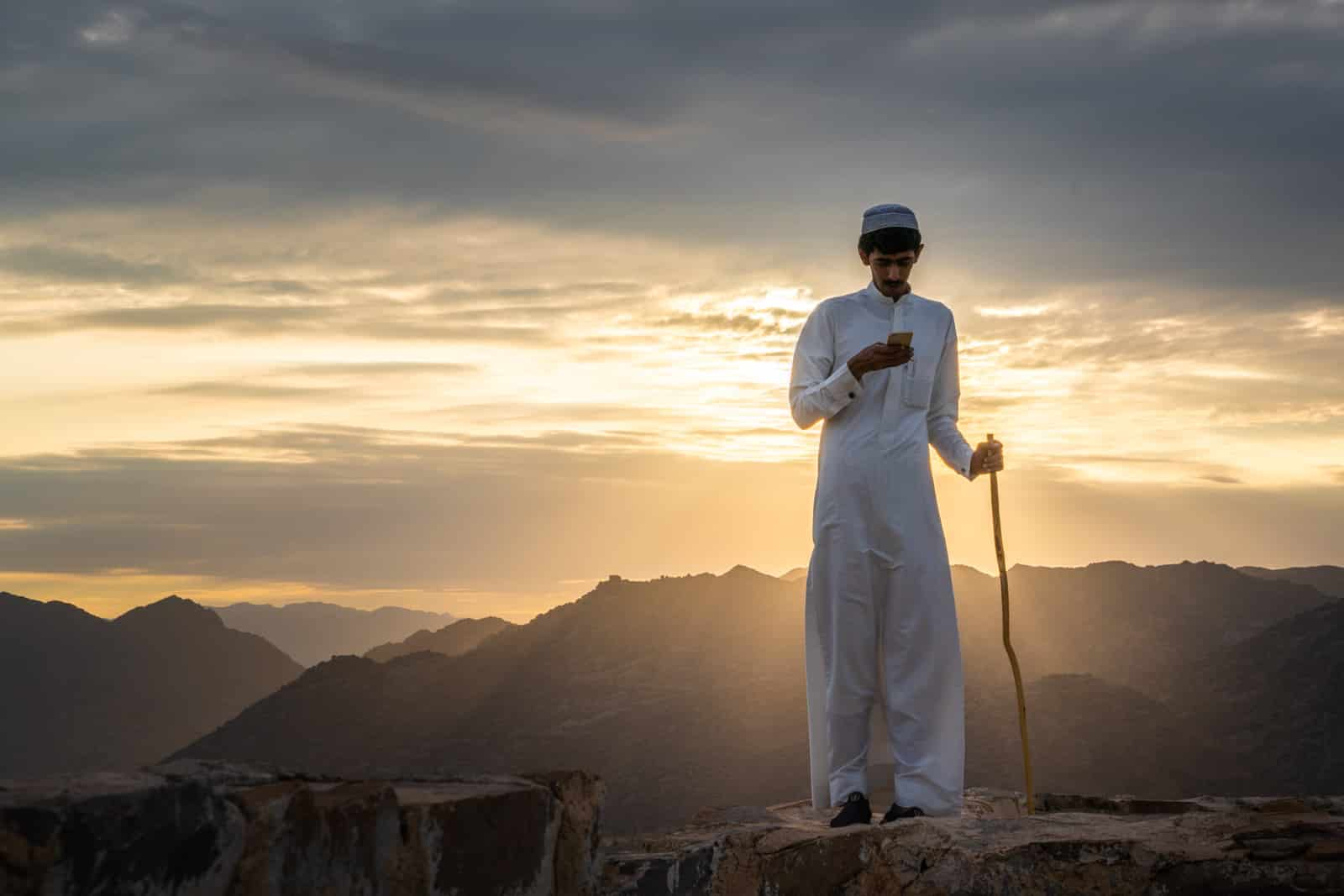 Boy using his mobile phone during sunset in Najran, Saudi Arabia