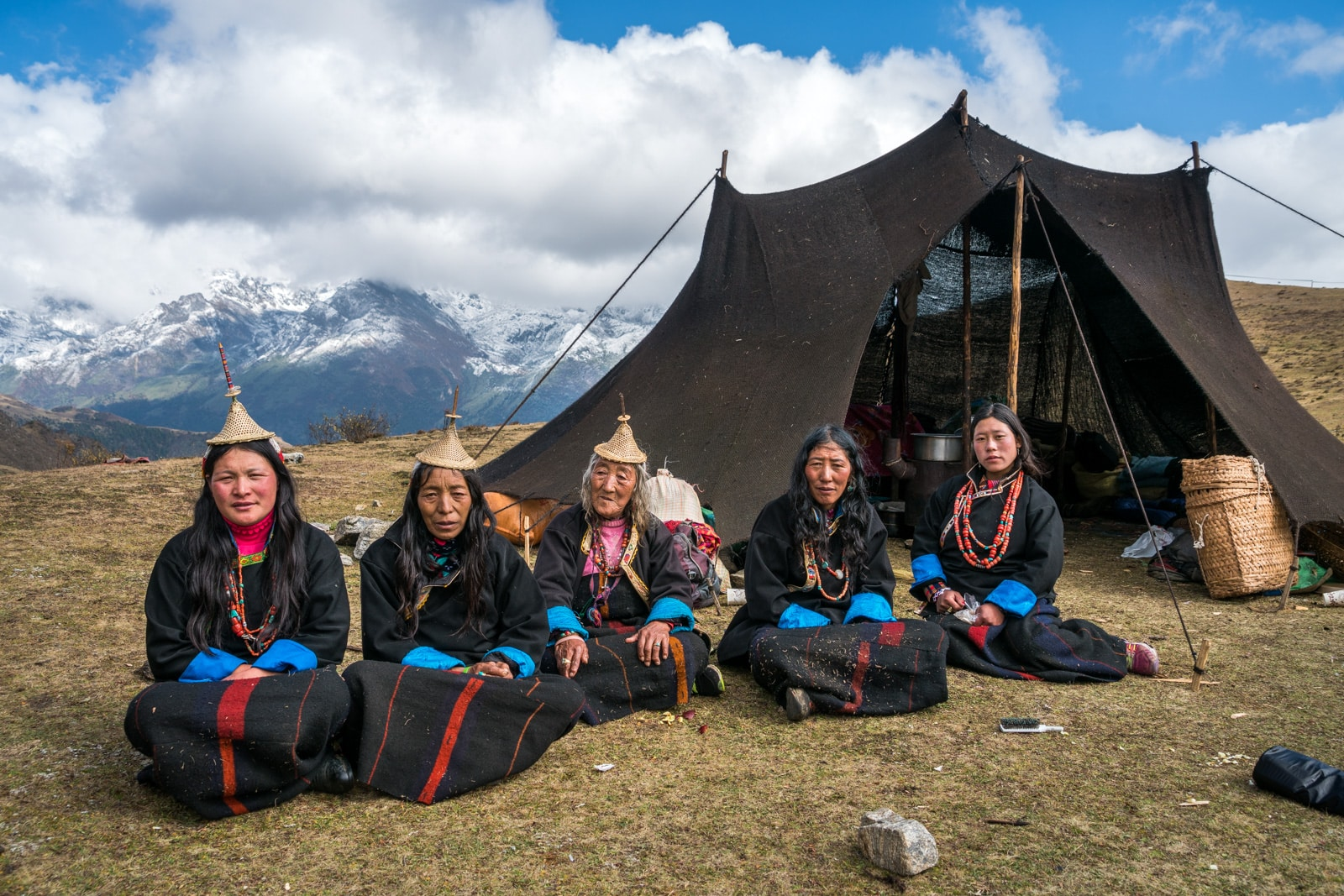 Layap women sitting in front of a yak hair tent at the Royal Highlander festival
