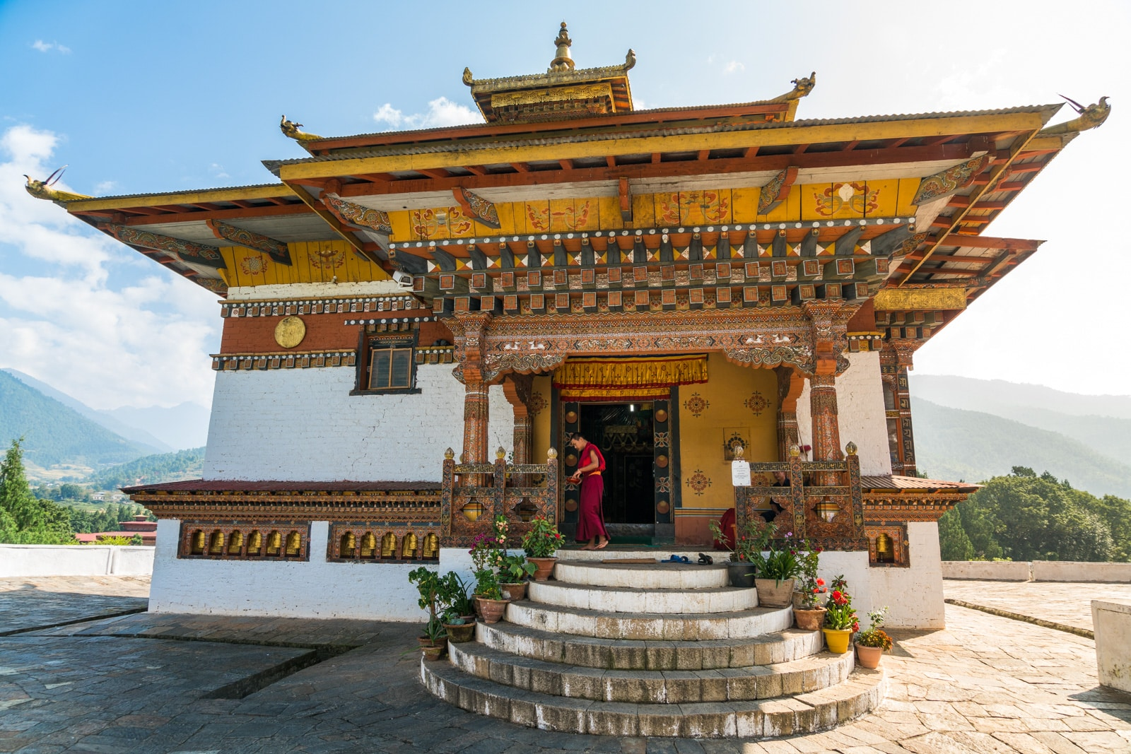 Monk standing on the doorway of a small monastery in Punakha