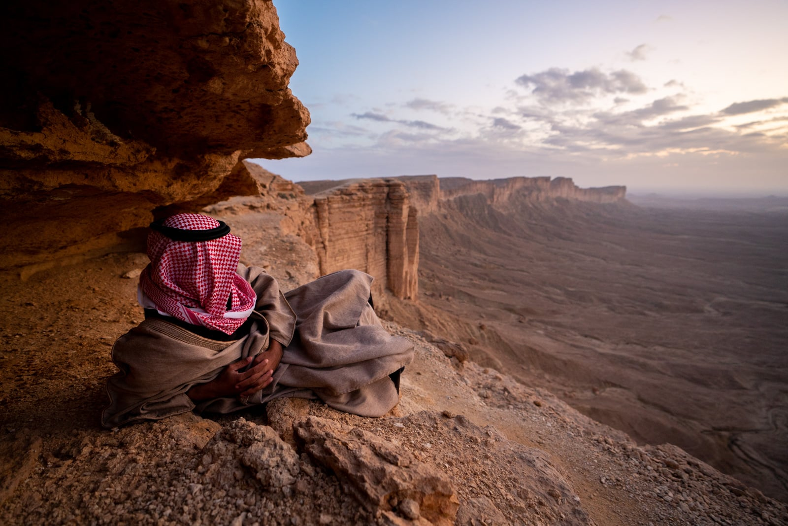 Saudi man sitting at the Edge of the World near Riyadh, Saudi Arabia, at sunset