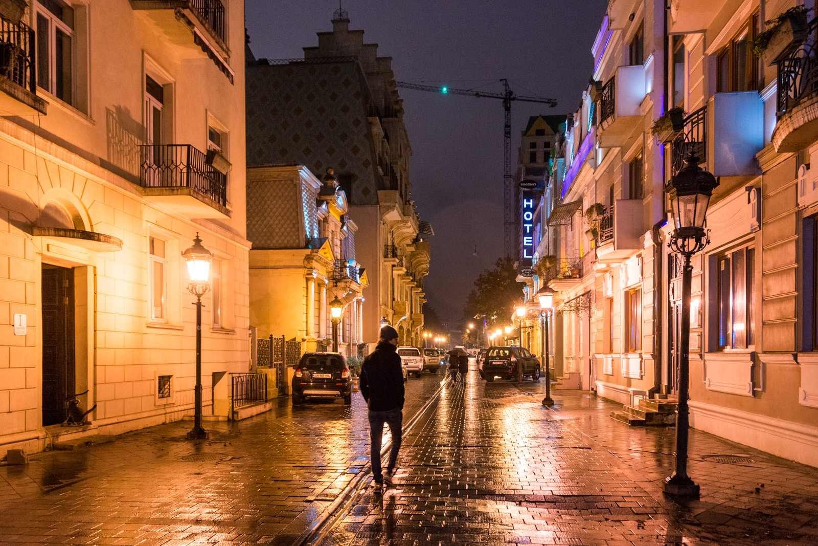 Man walking on the street at night in Batumi, Georgia