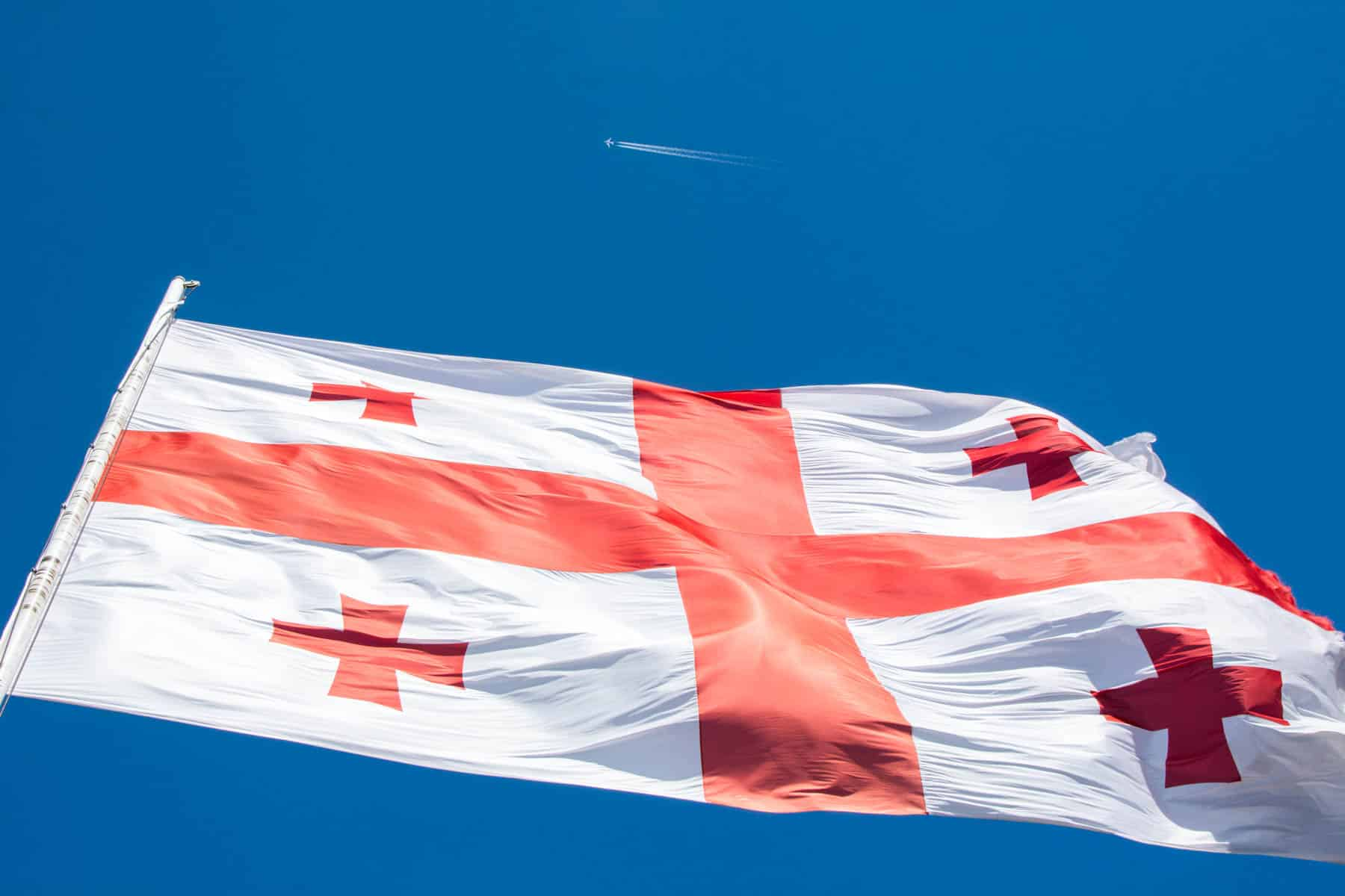 Plane flying over Georgian flag