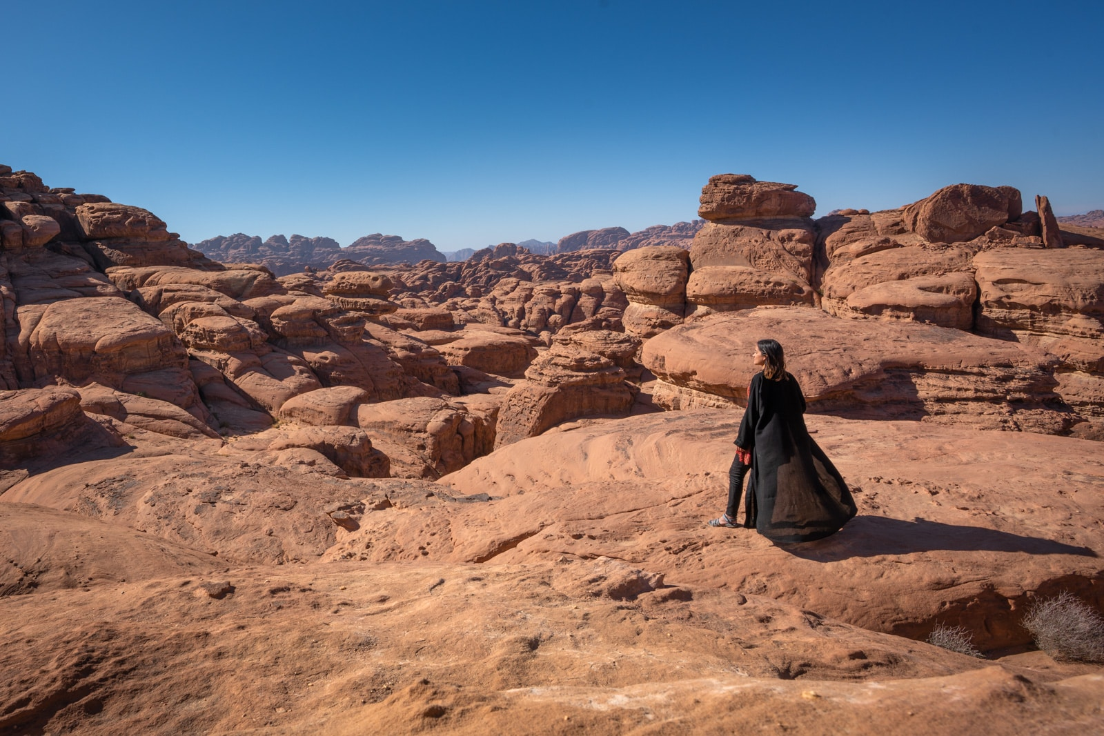 Female traveler climbing rocks in northern Saudi Arabia