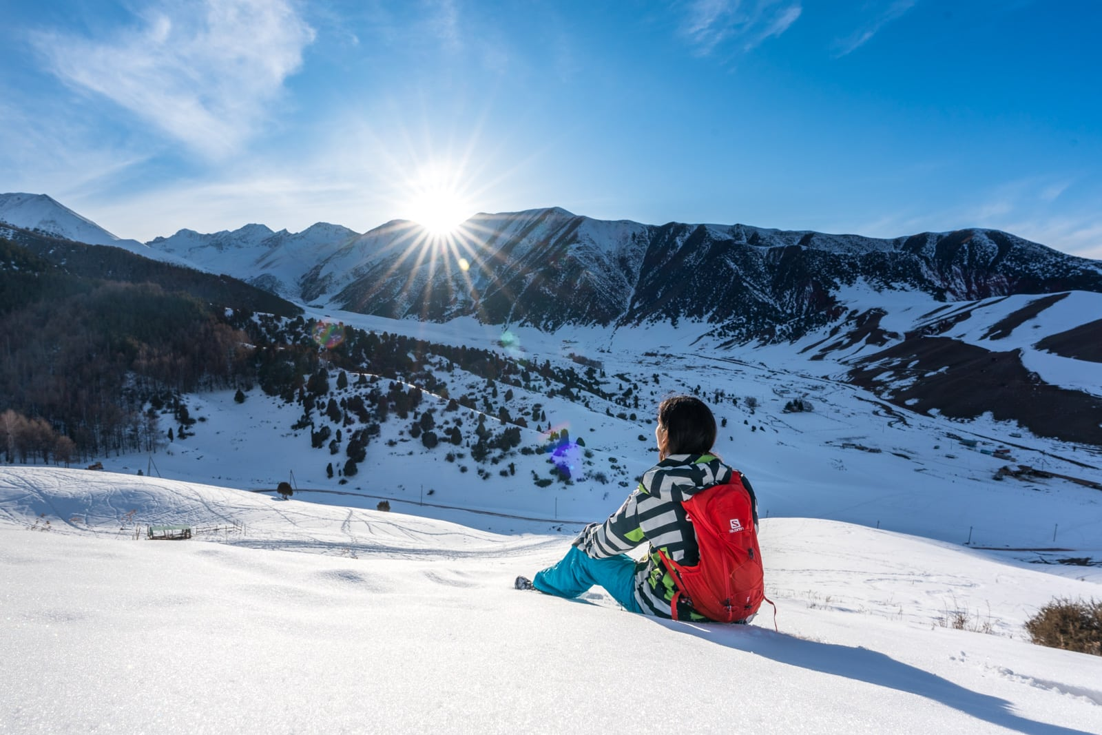 Female travel blogger sitting in the snow in Kyrgyzstan