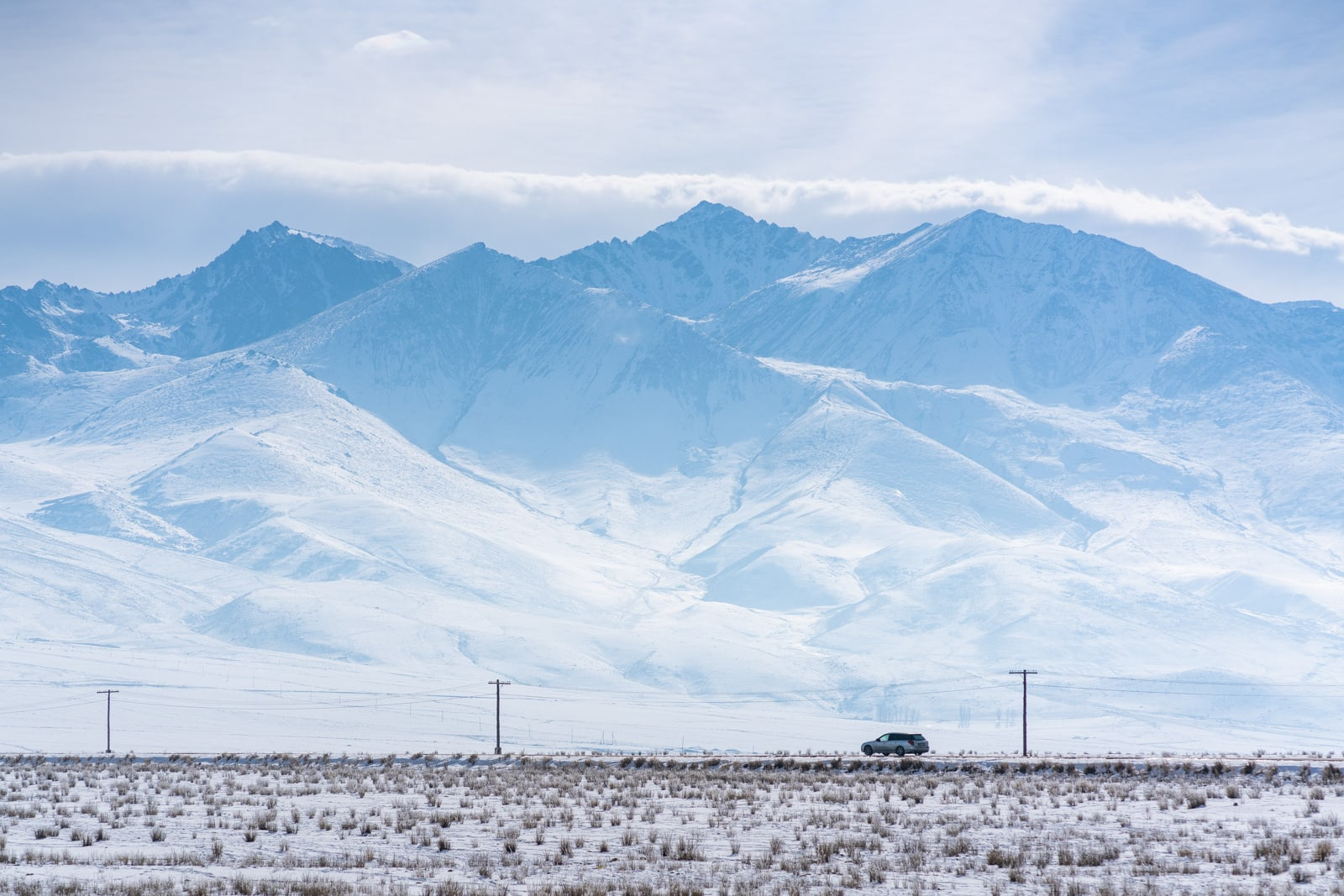 Car driving on the road on the south shore of Lake Issyk Kul, Kyrgyzstan