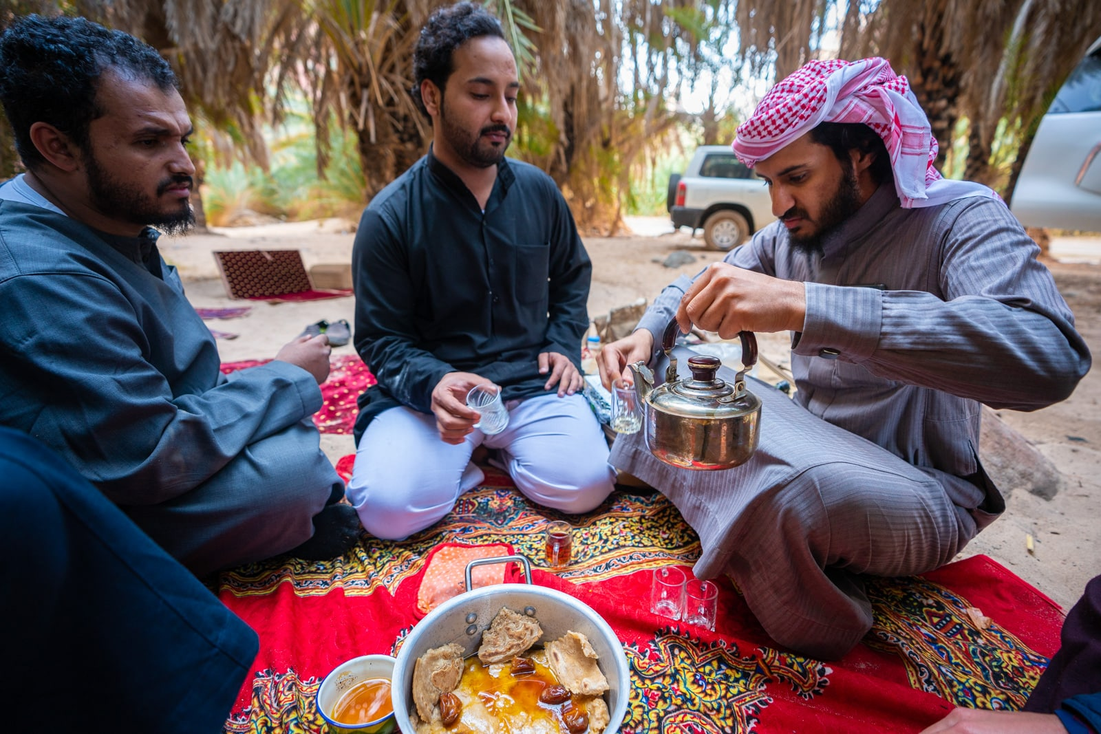 Saudi men eating on the ground while camping.