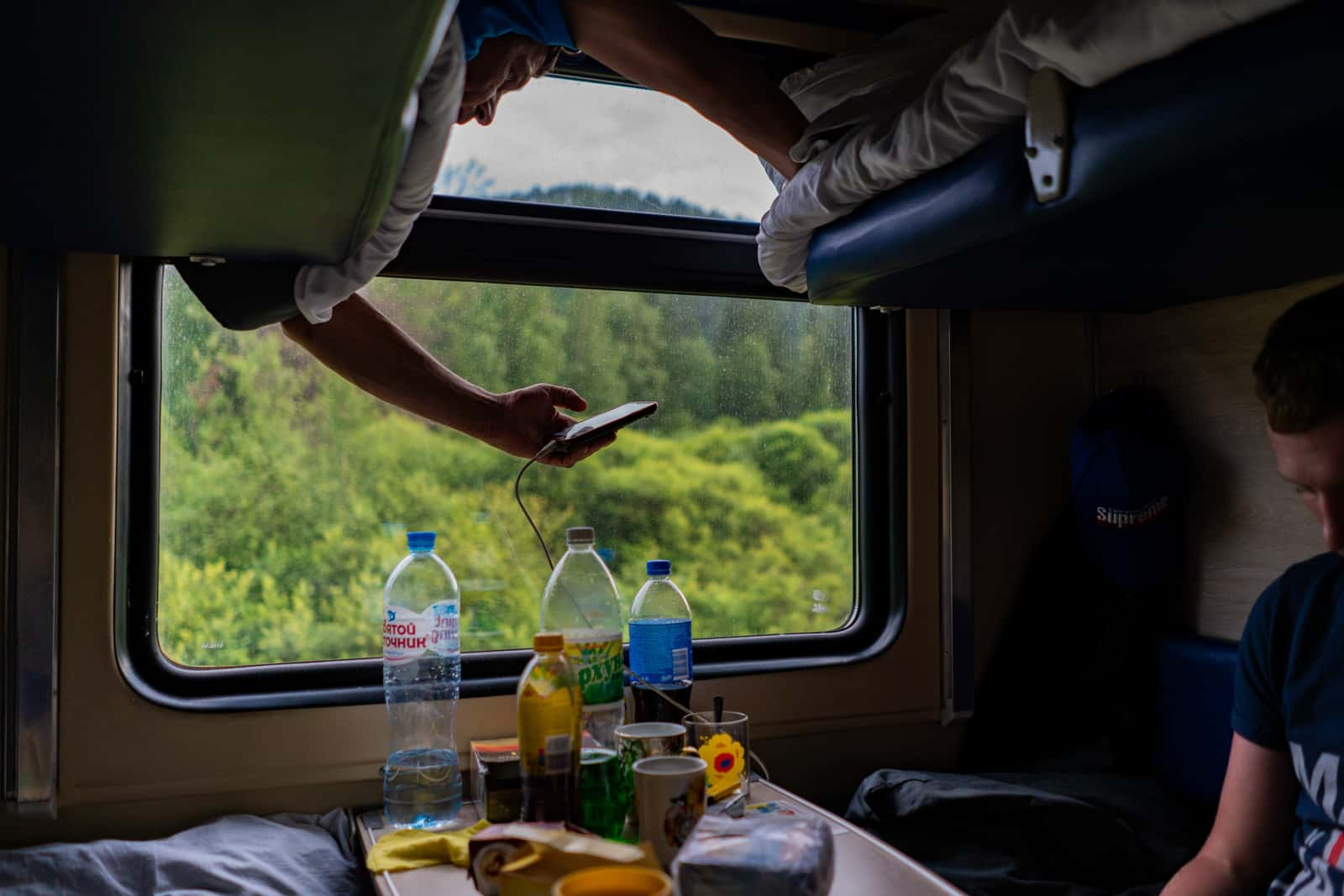 Man using mobile phone charger on Russian train