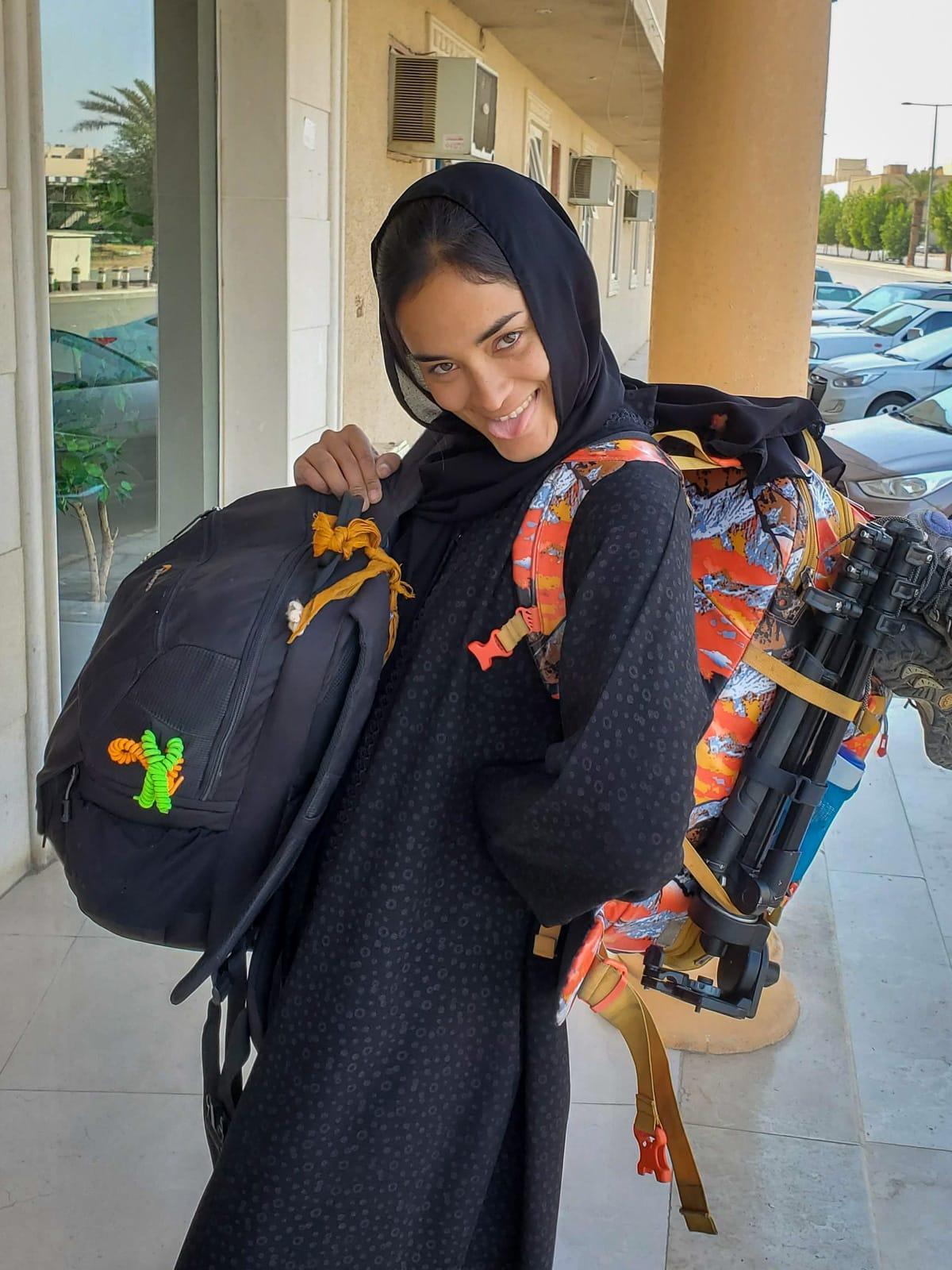 Alex with camera bag and backpack in a black abaya in Riyadh, Saudi Arabia
