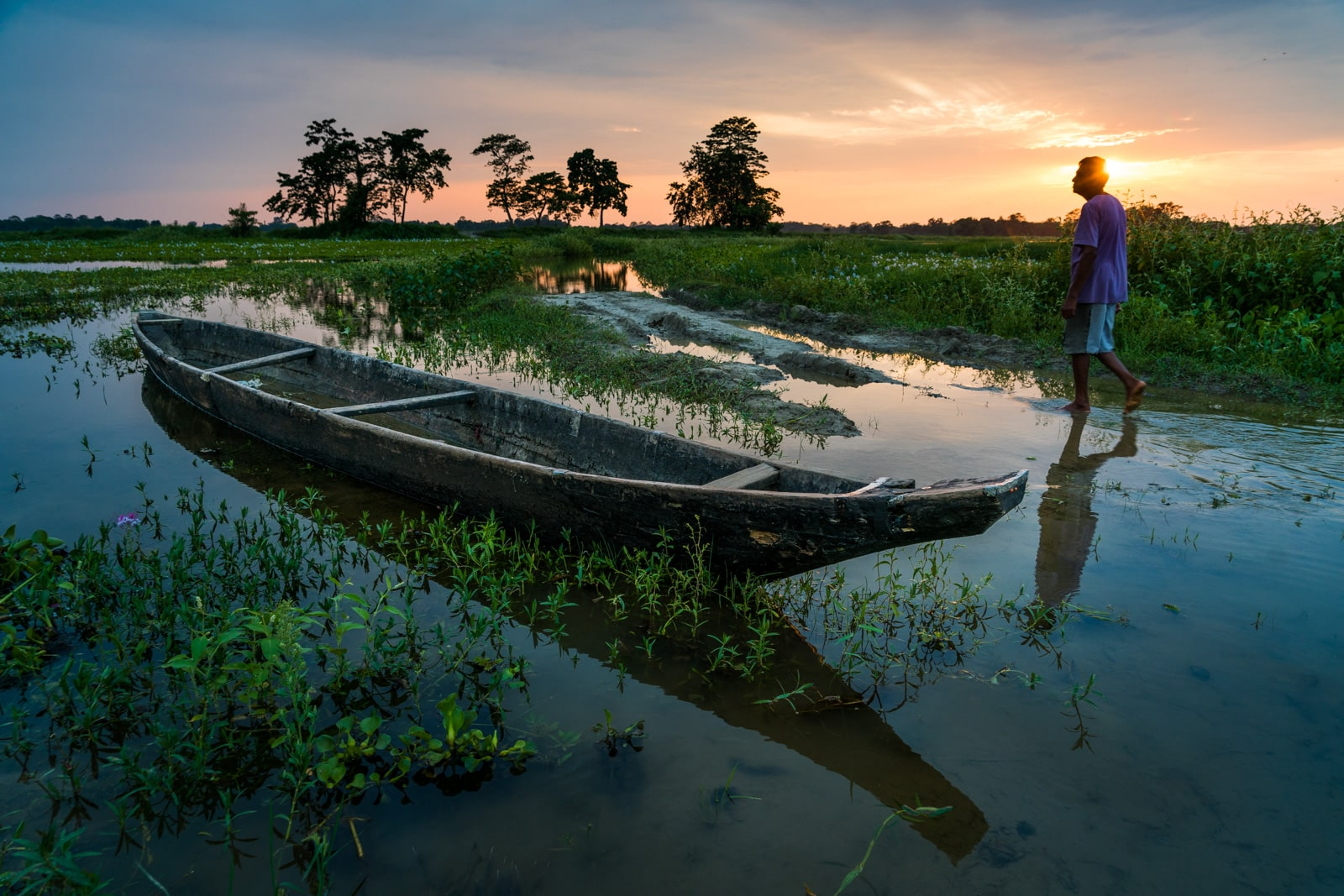 Man walking by a boat on Majuli Island, India