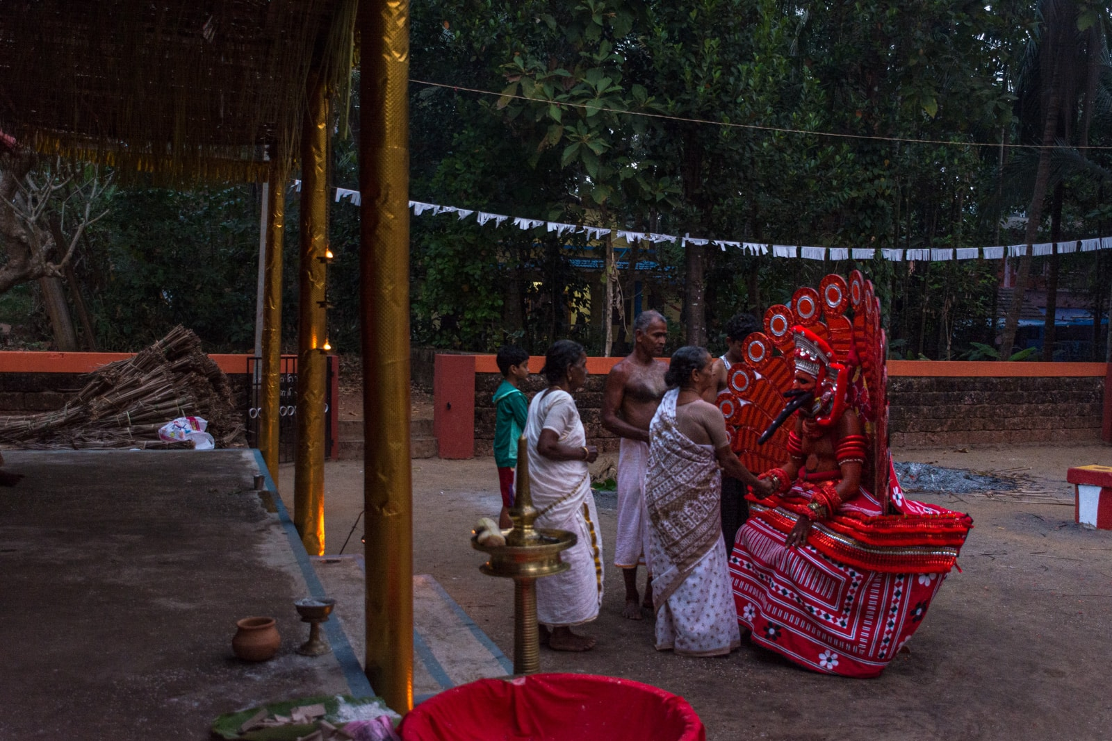 People giving offerings to a theyyam dancer in Kerala, India